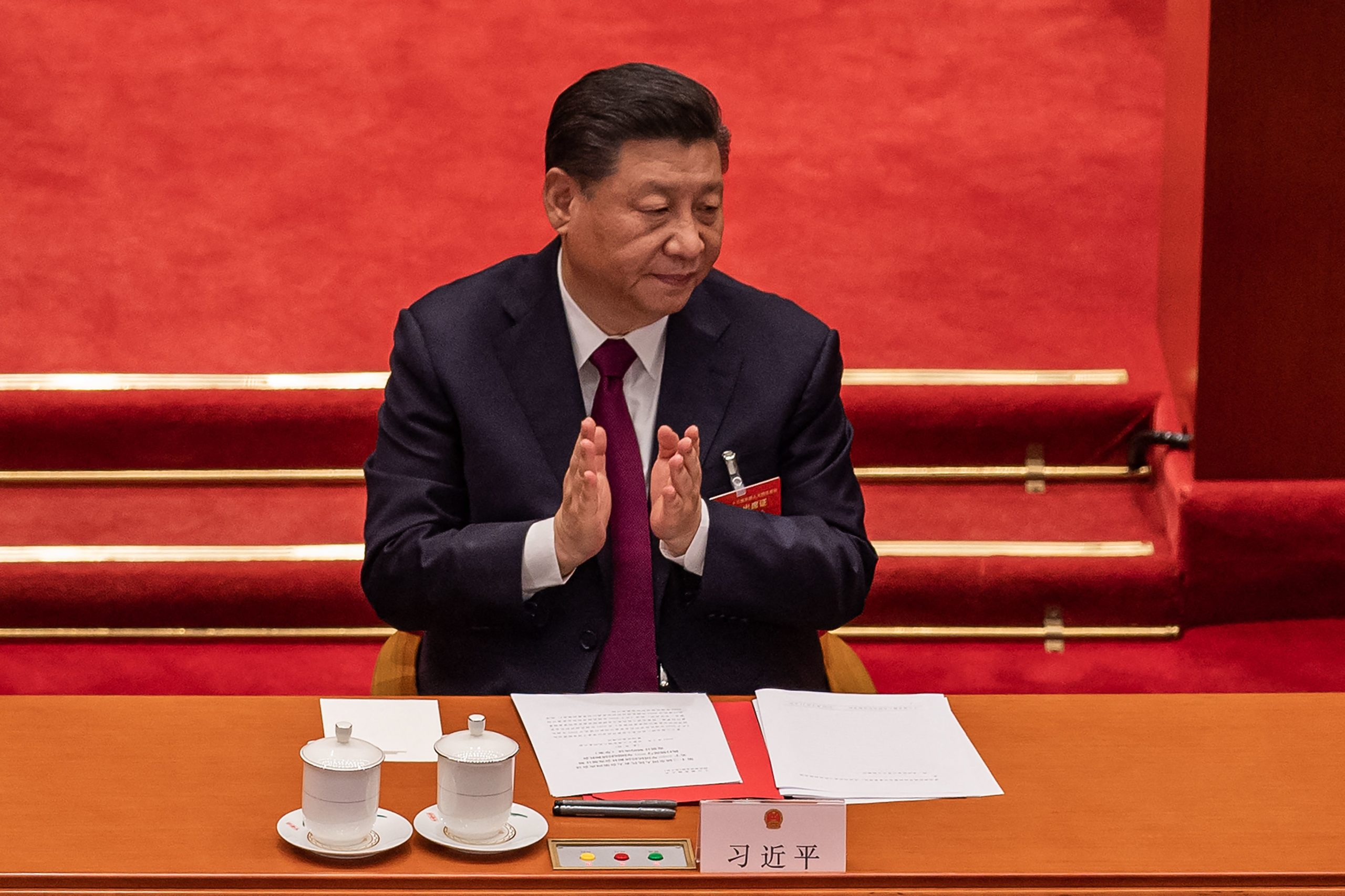 China's President Xi Jinping applauds after the result of the vote on changes to Hong Kong's election system was announced during the closing session of the National Peoples Congress (NPC) at the Great Hall of the People in Beijing on March 11, 2021. (Photo by NICOLAS ASFOURI/AFP via Getty Images)