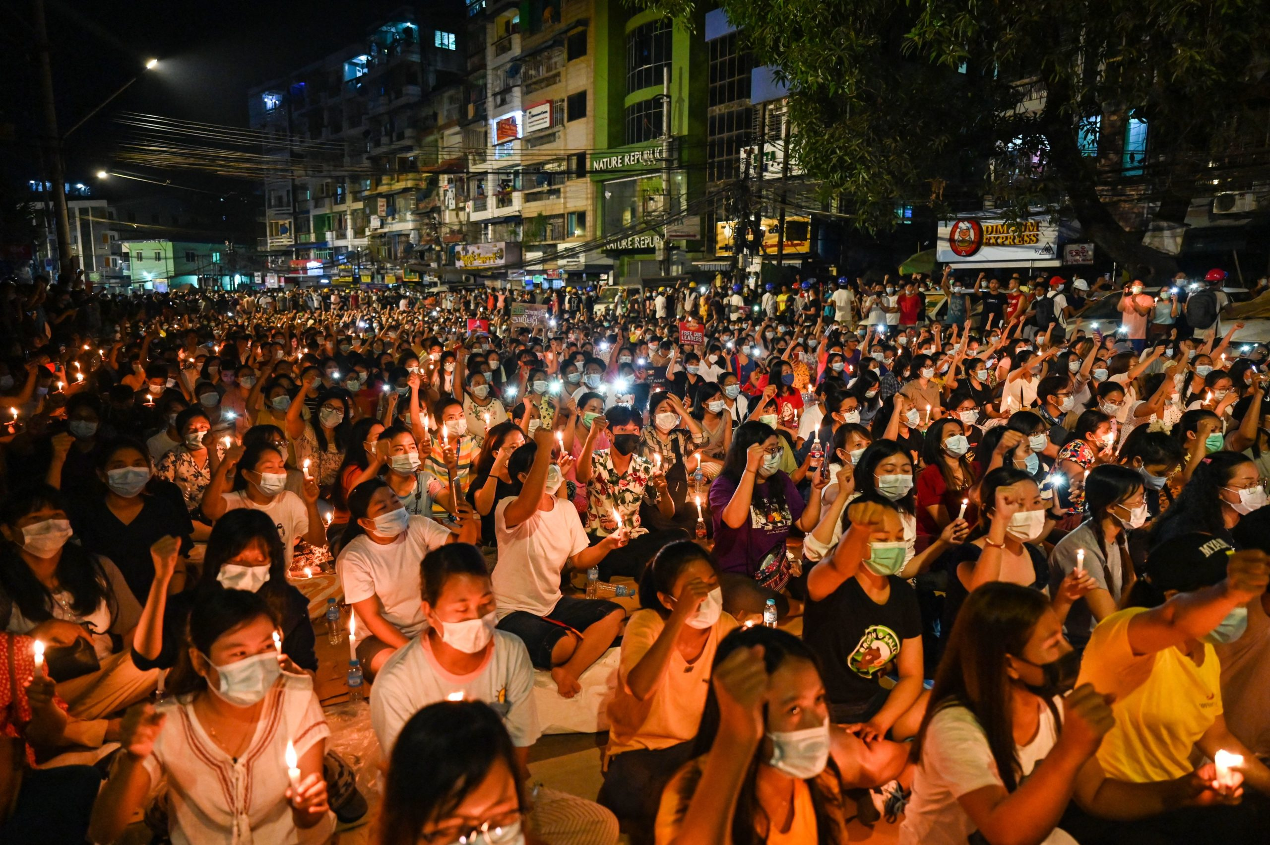 Protesters gesture during a candlelight vigil to honour those who have died during demonstrations against the military coup in Yangon on March 13, 2021. (Photo by STR / AFP) (Photo by STR/AFP via Getty Images)