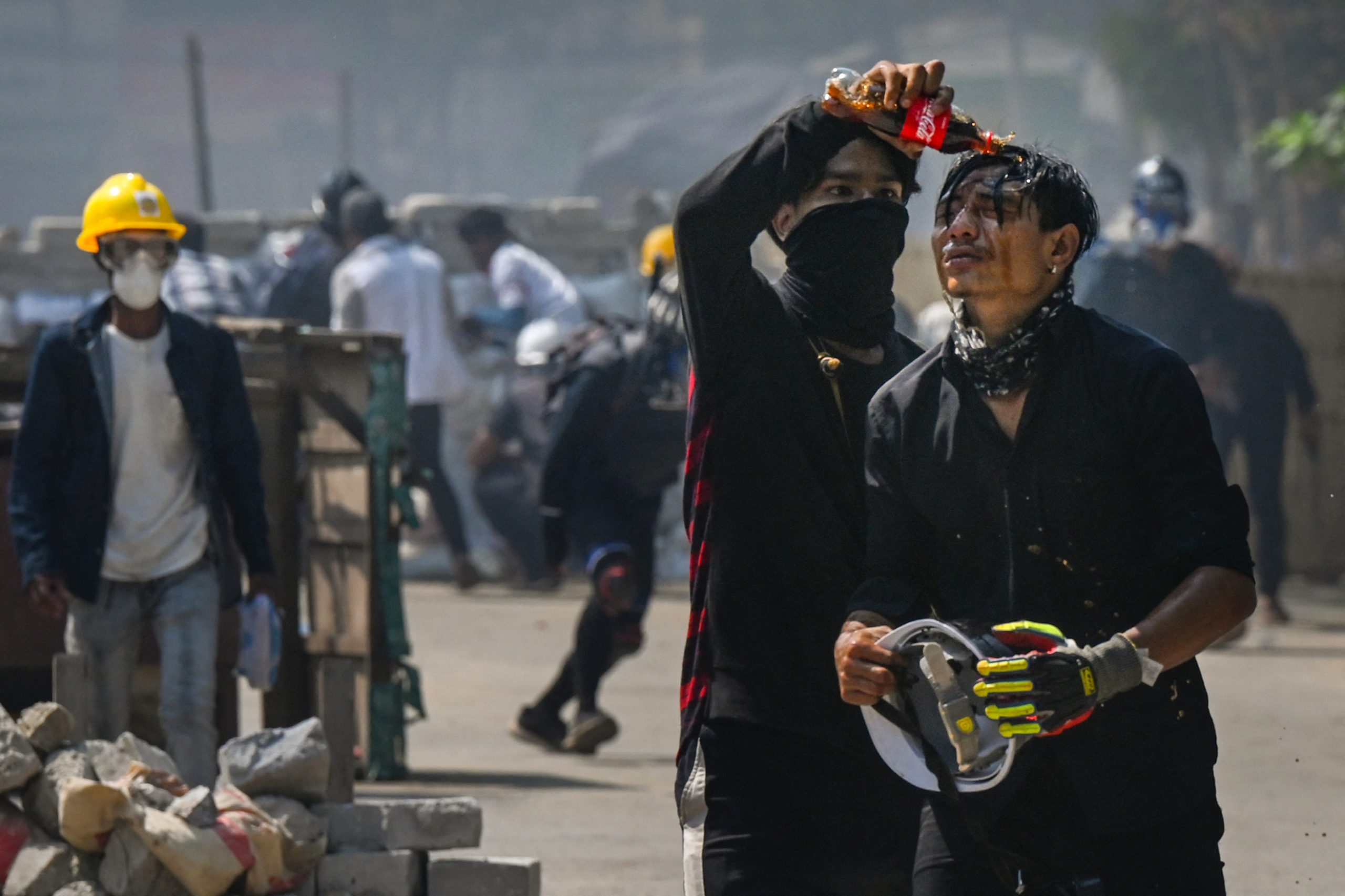 TOPSHOT - A protester pours Coca-Cola on the face of a comrade to diminish the effects of tear gas during a crackdown by security forces on a demonstration against the military coup in Yangon's Thaketa township on March 19, 2021. (Photo by STR / AFP) (Photo by STR/AFP via Getty Images)