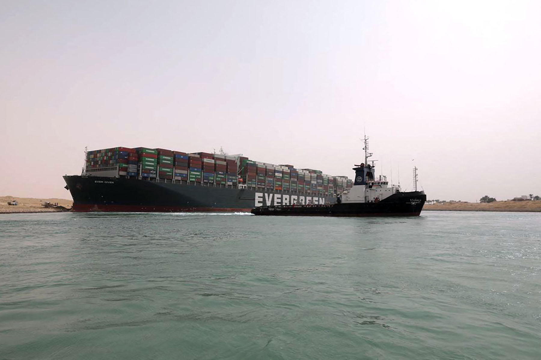 A handout picture released by the Suez Canal Authority on March 25, 2021 shows the MV Ever Given (Evergreen), a 400-metre- (1,300-foot-)long and 59-metre wide vessel, lodged sideways and impeding all traffic across the waterway of Egypt's Suez Canal. - Egypt's Suez Canal Authority said it was