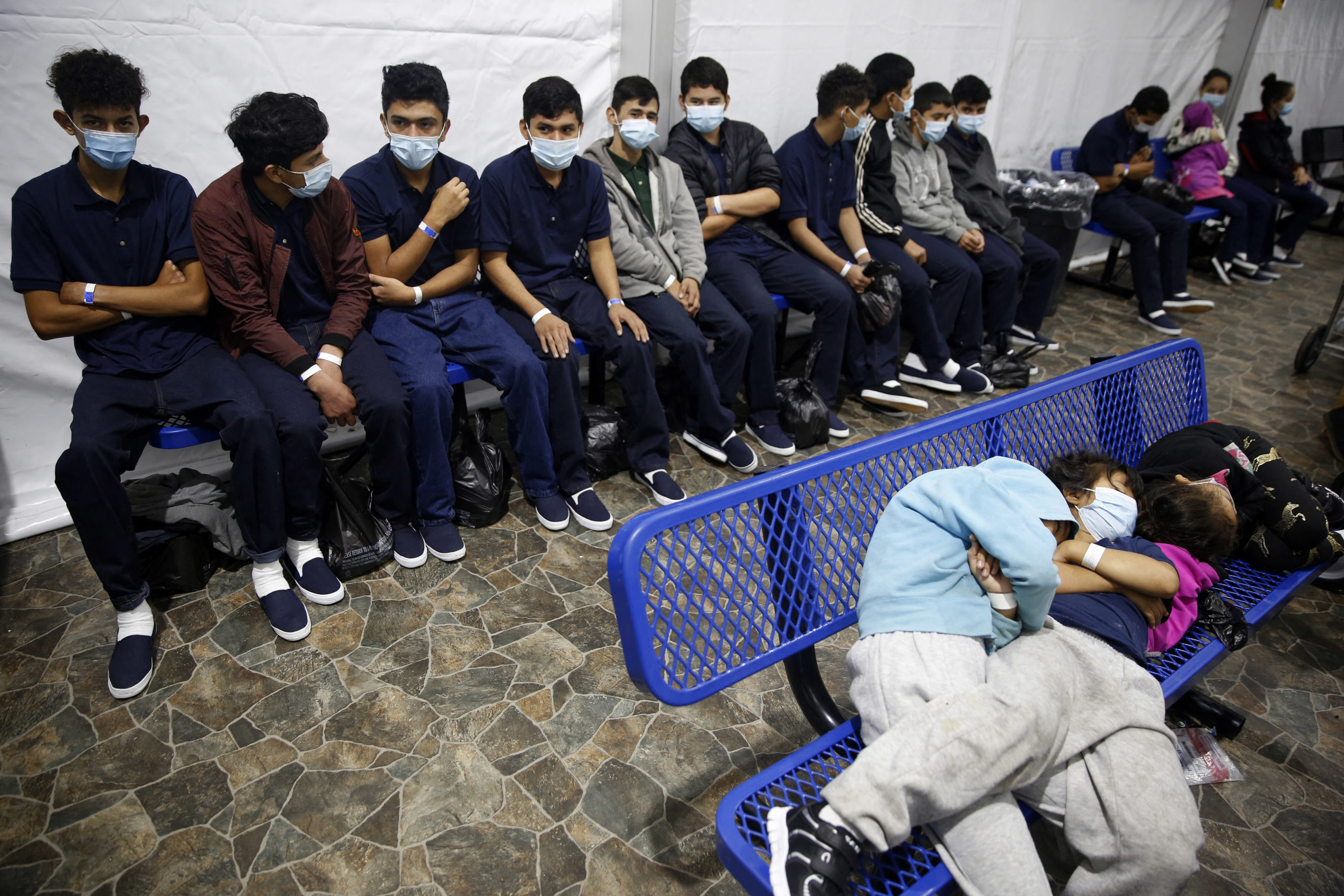 Young unaccompanied migrants, wait for their turn at the secondary processing station inside the Donna Department of Homeland Security holding facility, the main detention center for unaccompanied children in the Rio Grande Valley in Donna, Texas on March 30, 2021. - The Biden administration on Tuesday for the first time allowed journalists inside its main detention facility at the border for migrant children, revealing a severely overcrowded tent structure where more than 4,000 kids and families were crammed into pods and the youngest kept in a large play pen with mats on the floor for sleeping. (Photo by Dario Lopez-Mills / POOL / AFP) (Photo by DARIO LOPEZ-MILLS/POOL/AFP via Getty Images)