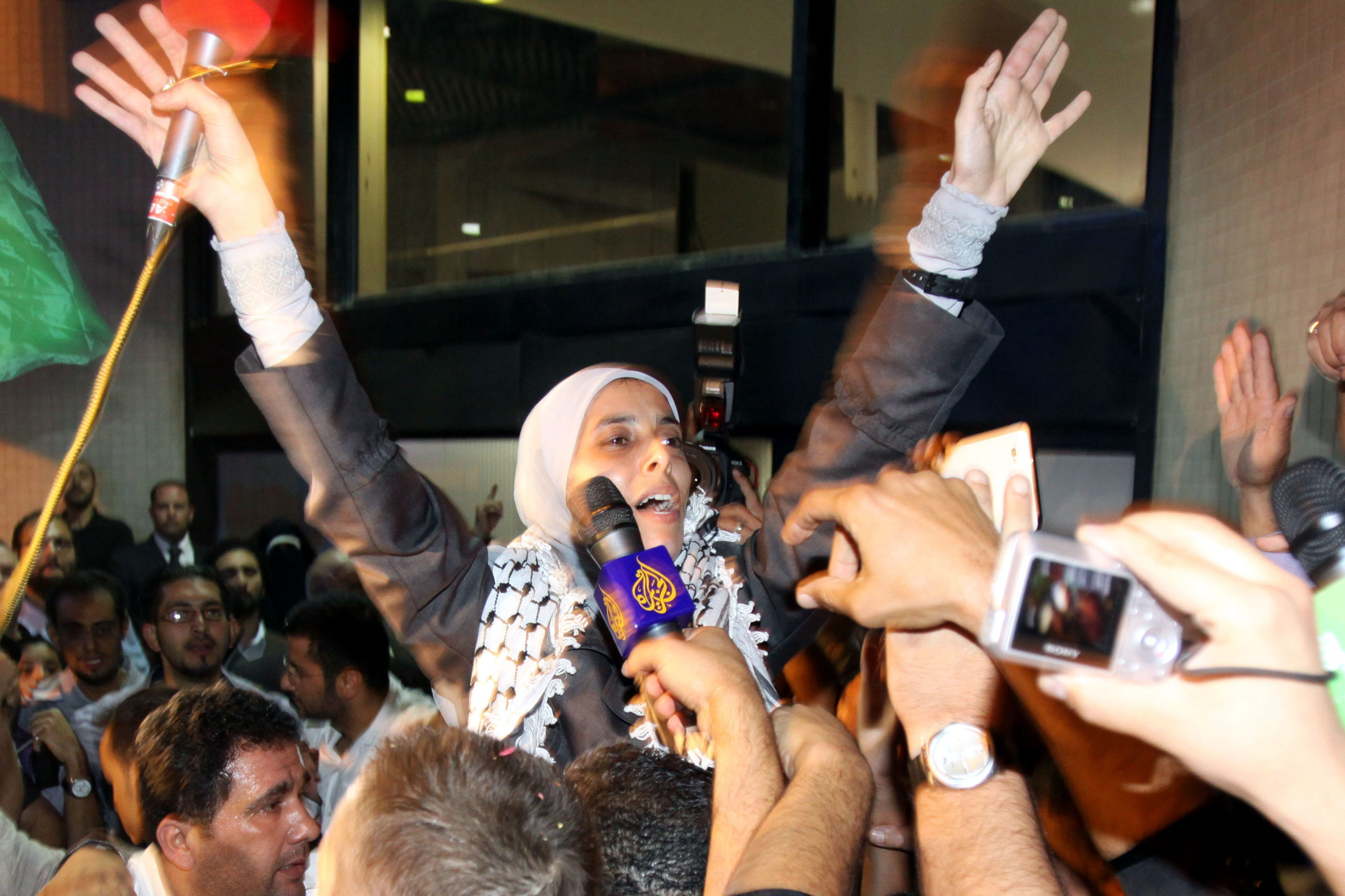 Jordanian freed prisoner Ahlam Tamimi waves as she arrives at Queen Alia international airport in Amman, late October 18, 2011. Ahlam was sentenced to 16 life terms in jail for her involvement in attacks on the Sbarro Pizzeria in Jerusalem in August 2001. The Palestinian Hamas movement exchanged Gilad Shalit, the Israeli soldier who spent more than five years of isolation in a Gaza hide-out, for hundreds of Palestinian militants being held in palestinian jails. (Photo credits: LOUAI BESHARA/AFP via Getty Images)