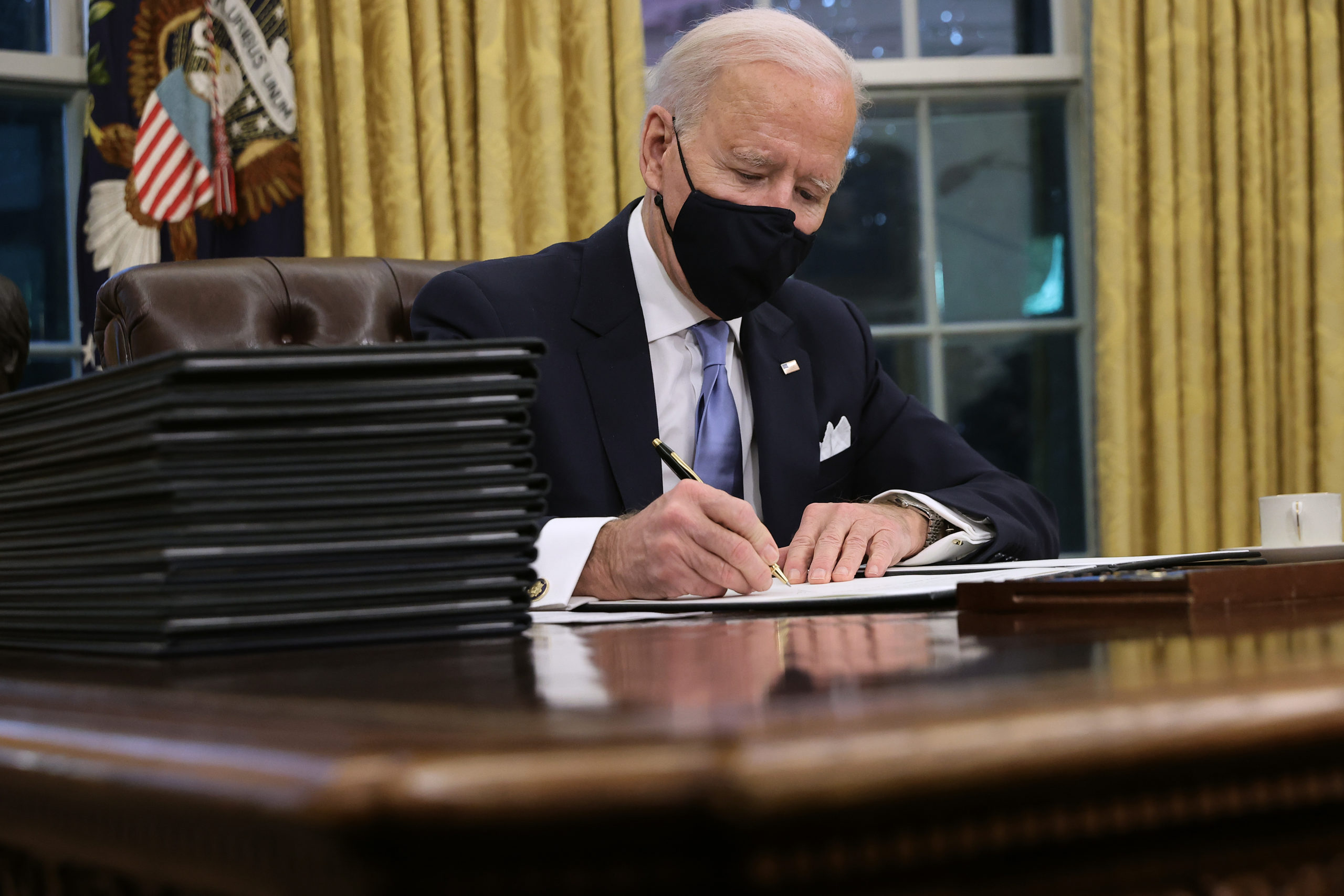 President Joe Biden prepares to sign a series of executive orders on Jan. 20. (Chip Somodevilla/Getty Images)