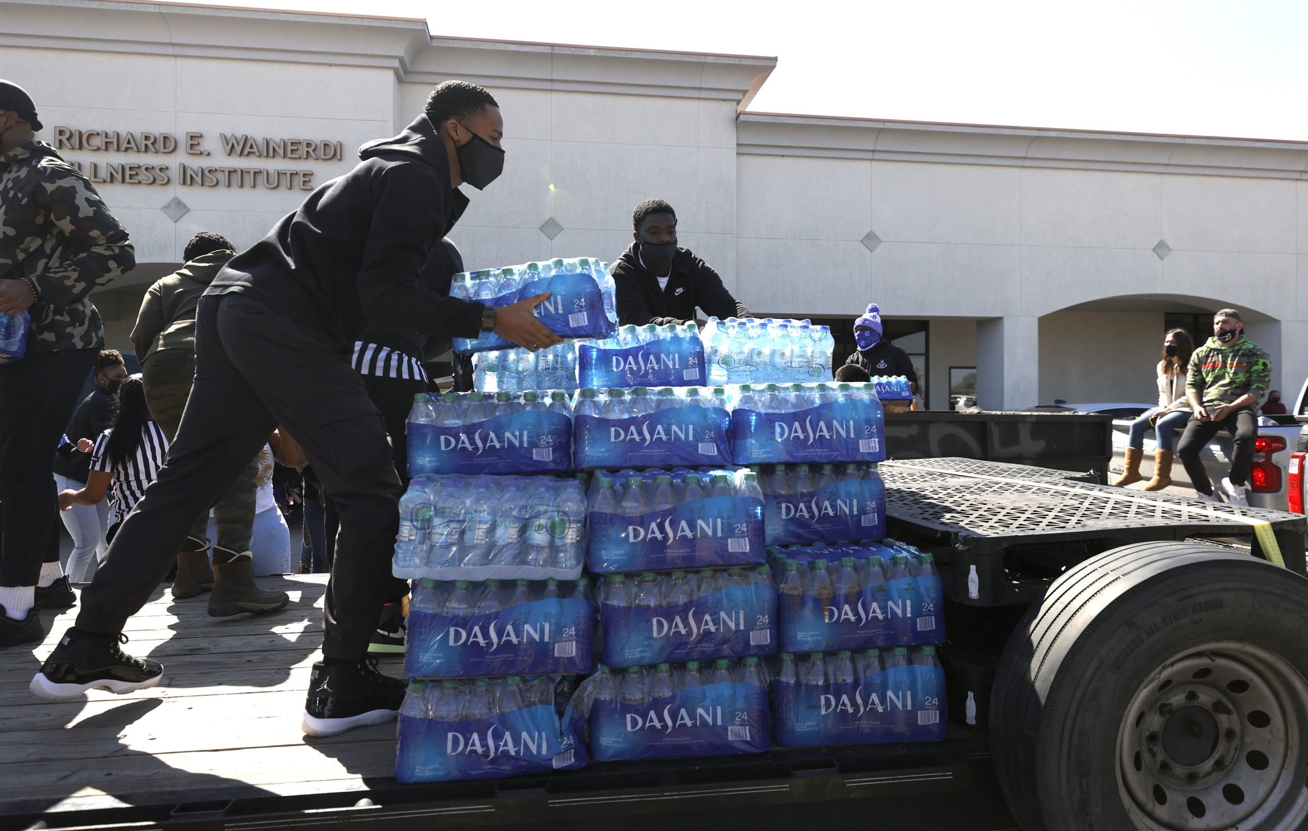 Volunteers stack cases of water during a water distribution event at the Fountain Life Center on February 20, 2021 in Houston, Texas. Much of Texas is still struggling with historic cold weather, power outages and a shortage of potable water after winter storm Uri swept across 26 states with a mix of freezing temperatures and precipitation. Many Houston residents do not have drinkable water at their homes and are relying on city water giveaways. (Photo by Justin Sullivan/Getty Images)