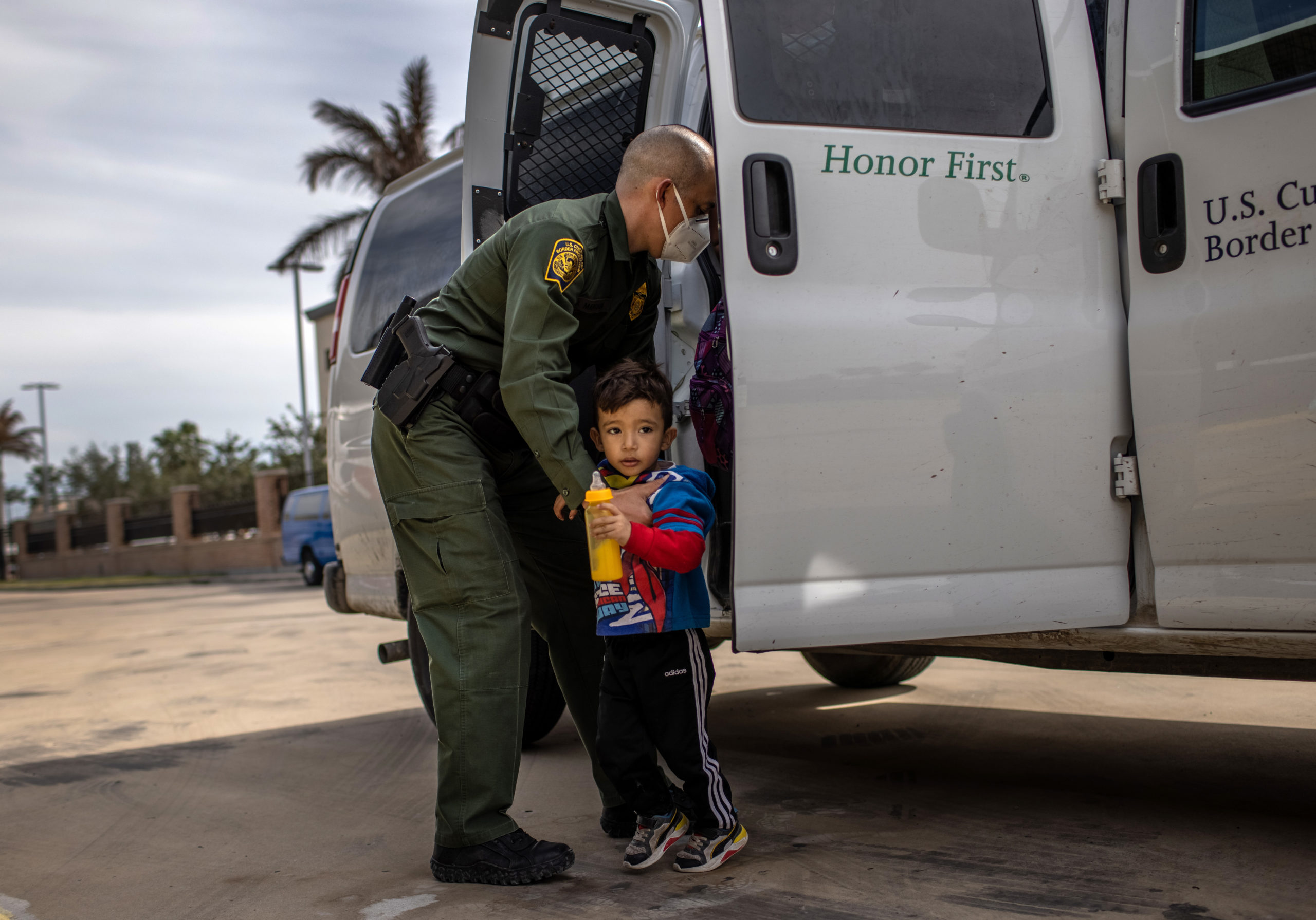 BROWNSVILLE, TEXAS - FEBRUARY 26: A U.S. Border Patrol agent delivers a young asylum seeker and his family to a bus station on February 26, 2021 in Brownsville, Texas. U.S. immigration authorities are now releasing many asylum seeking families after detaining them while crossing the U.S.-Mexico border. The immigrant families are then free to travel to destinations throughout the U.S. while awaiting asylum hearings. (Photo by John Moore/Getty Images)