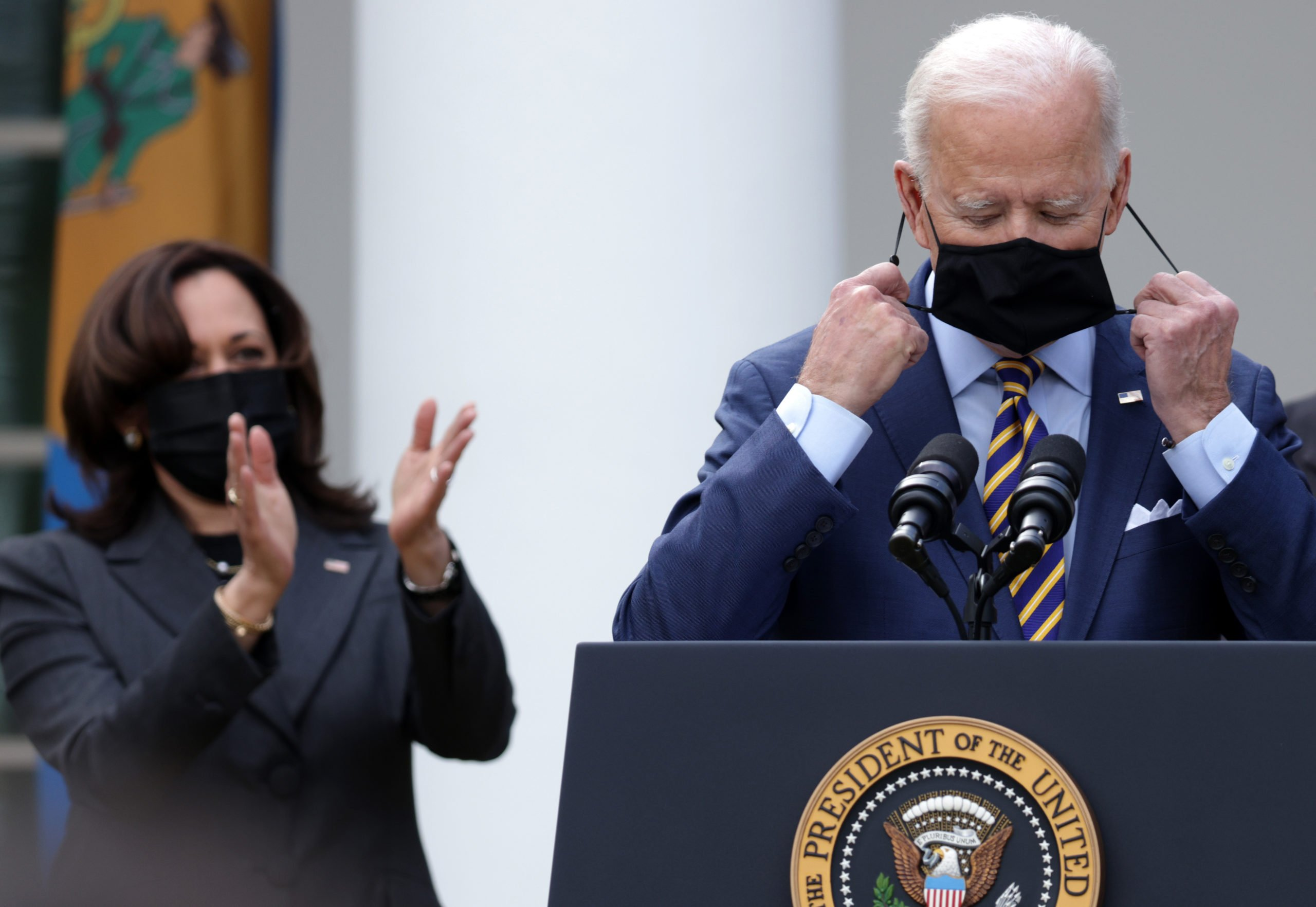 WASHINGTON, DC - MARCH 12: U.S. President Joe Biden (R) takes off his mask as Vice President Kamala Harris (L) looks on during an event on the American Rescue Plan in the Rose Garden of the White House on March 12, 2021 in Washington, DC. President Biden signed the $1.9 trillion American Rescue Plan Act into law that will send aid to millions of Americans struggling from the COVID-19 pandemic. (Photo by Alex Wong/Getty Images)