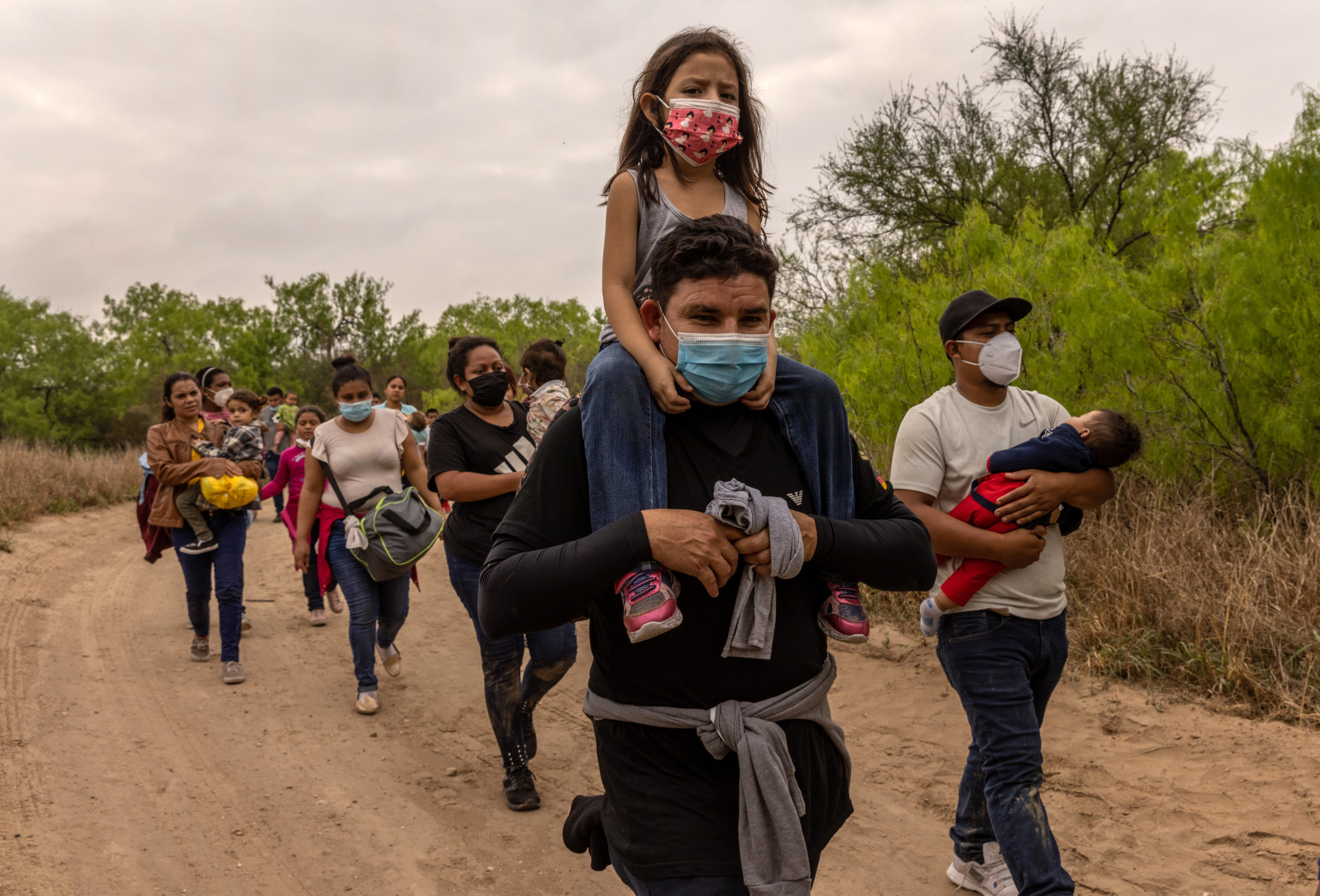 Asylum seekers, most from Honduras, walk towards a U.S. Border Patrol checkpoint after crossing the Rio Grande from Mexico on March 23, 2021 near Mission, Texas.(Photo by John Moore/Getty Images)