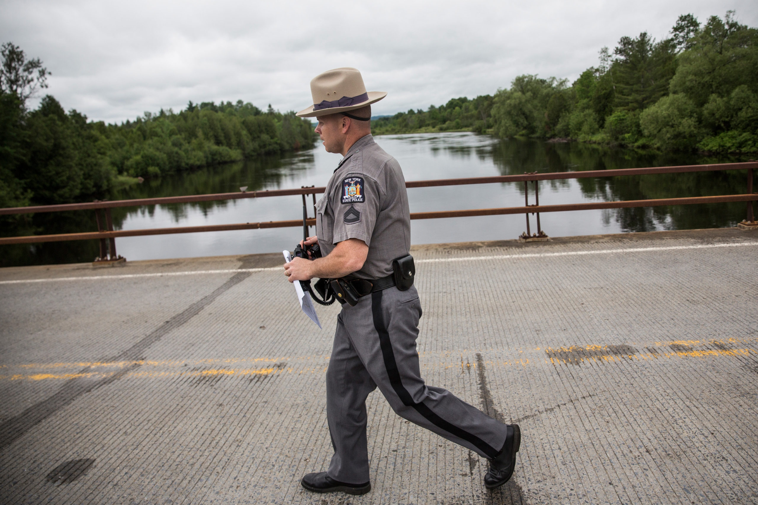 DANNEMORA, NY - JUNE 15: A New York state trooper walks across a bridge while searching for two escaped convicts on June 15, 2015 outside Dannemora, New York. The two convicted murderers escaped from Clinton Correctional Facility during the early morning hours of June 6; officials have been conducting a manhunt for the two since. (Photo by Andrew Burton/Getty Images)