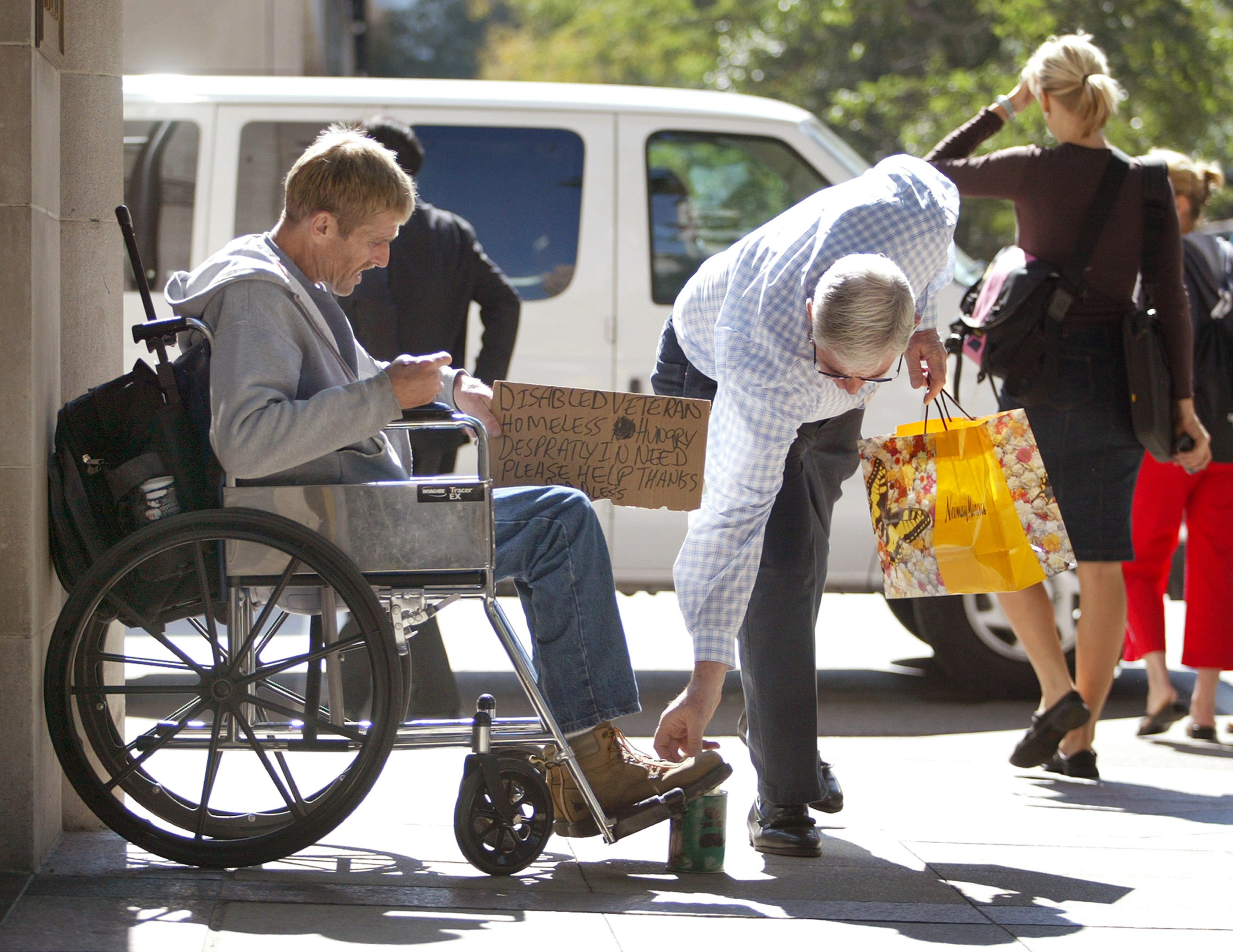 """A passerby drops some loose change into the can of a homeless, disabled veteran in his wheelchair looking for money along the shopping area known as the """"Magnificent Mile"""" on Michigan Ave. September 30, 2004 in Chicago. Chicago alderman are looking into an ordinance restricting areas of panhandling in the city. (Photo by Tim Boyle/Getty Images)"""