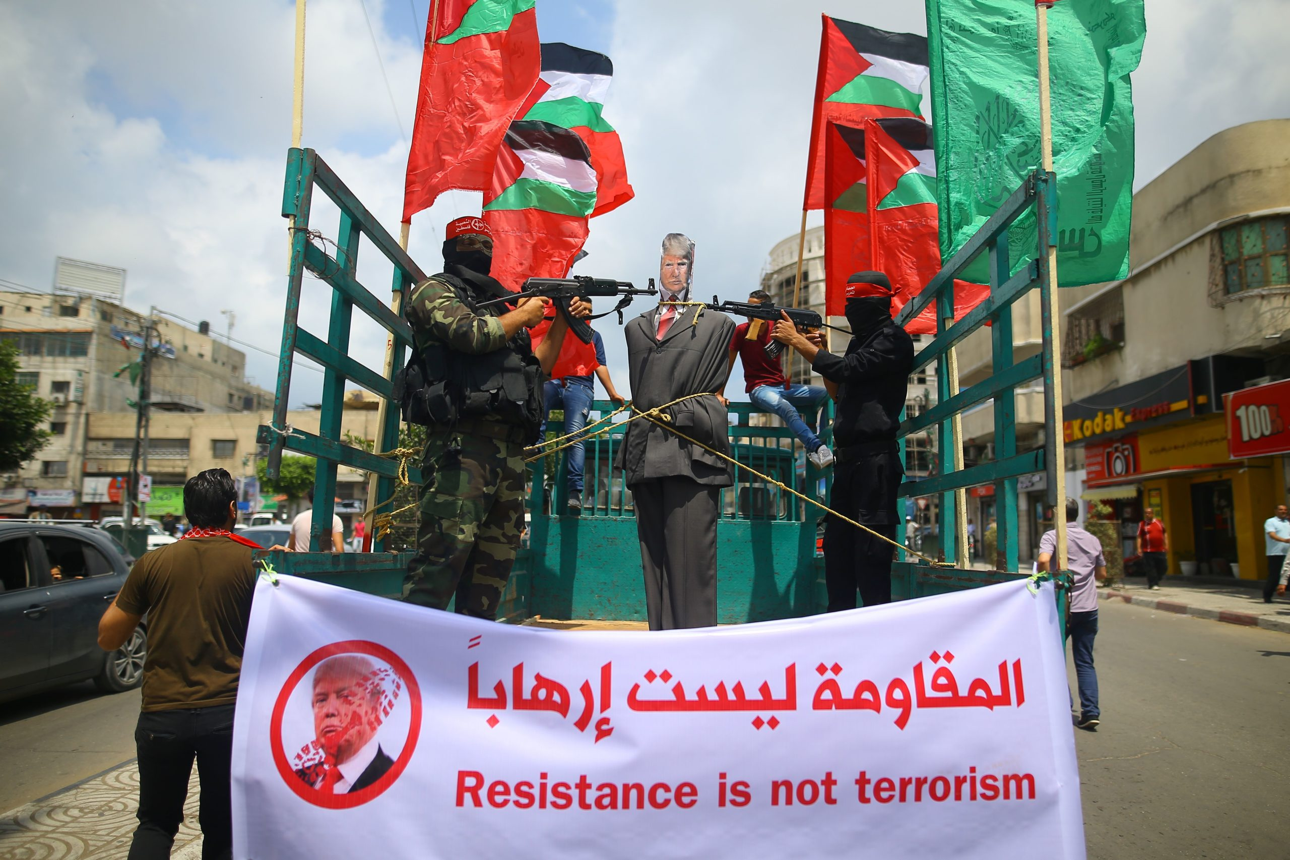 Palestinian militants from the Popular Front for the Liberation of Palestine (PFLP) aim their weapons at an effigy depicting US President Donald Trump as they ride a truck during a protest in Gaza City, on May 23, 2017. / AFP PHOTO / MOHAMMED ABED (Photo credit should read MOHAMMED ABED/AFP via Getty Images)
