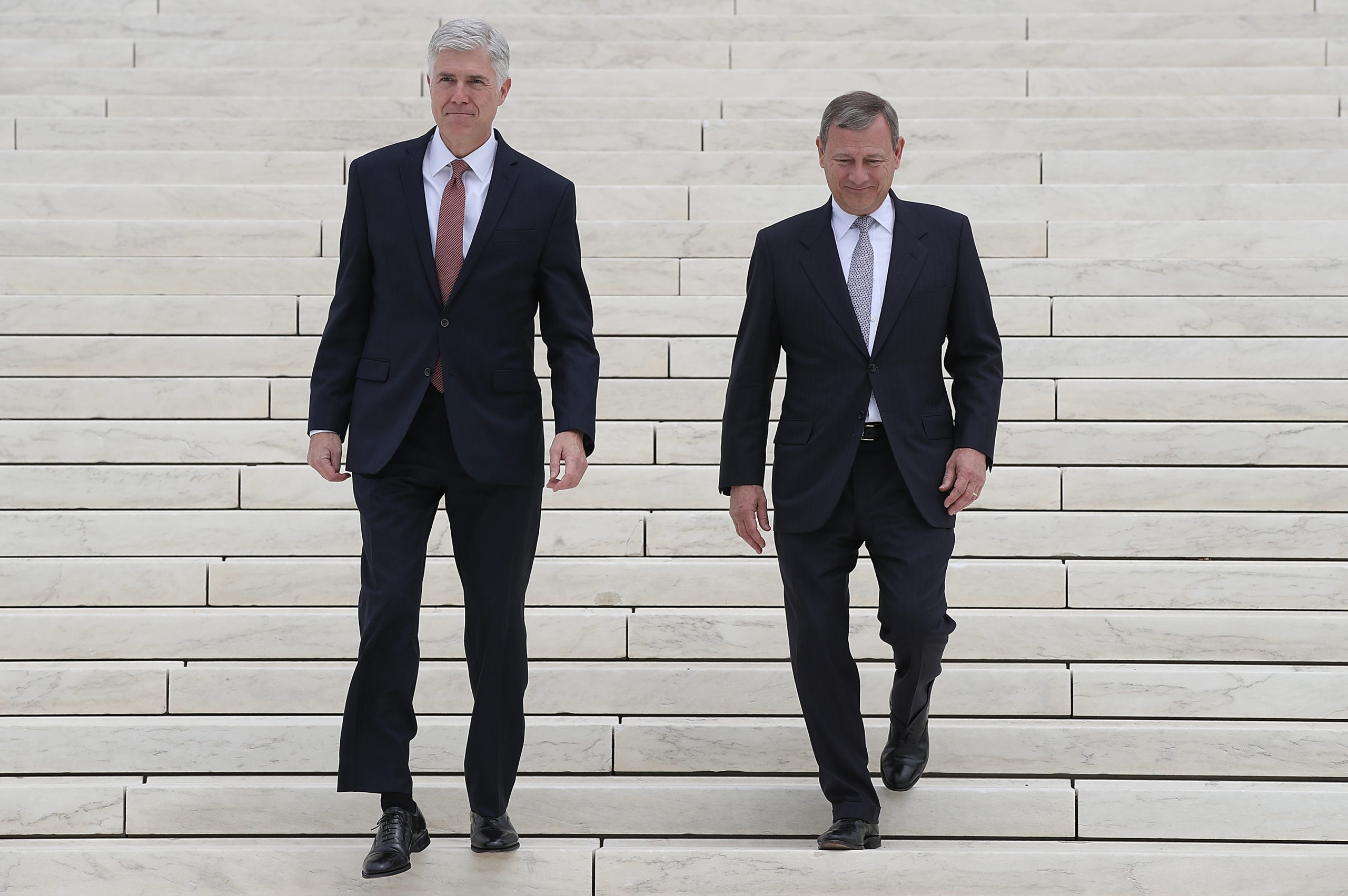 WASHINGTON, DC - JUNE 15: Supreme Court Justice Neil Gorsuch (L) walks down the steps of the Supreme Court with Chief Justice John Roberts (R) following his official investiture ceremony June 15, 2017 in Washington, DC. Gorsuch has been an active member of the court since his confirmation though the official investiture ceremony was held today. (Photo by Win McNamee/Getty Images)