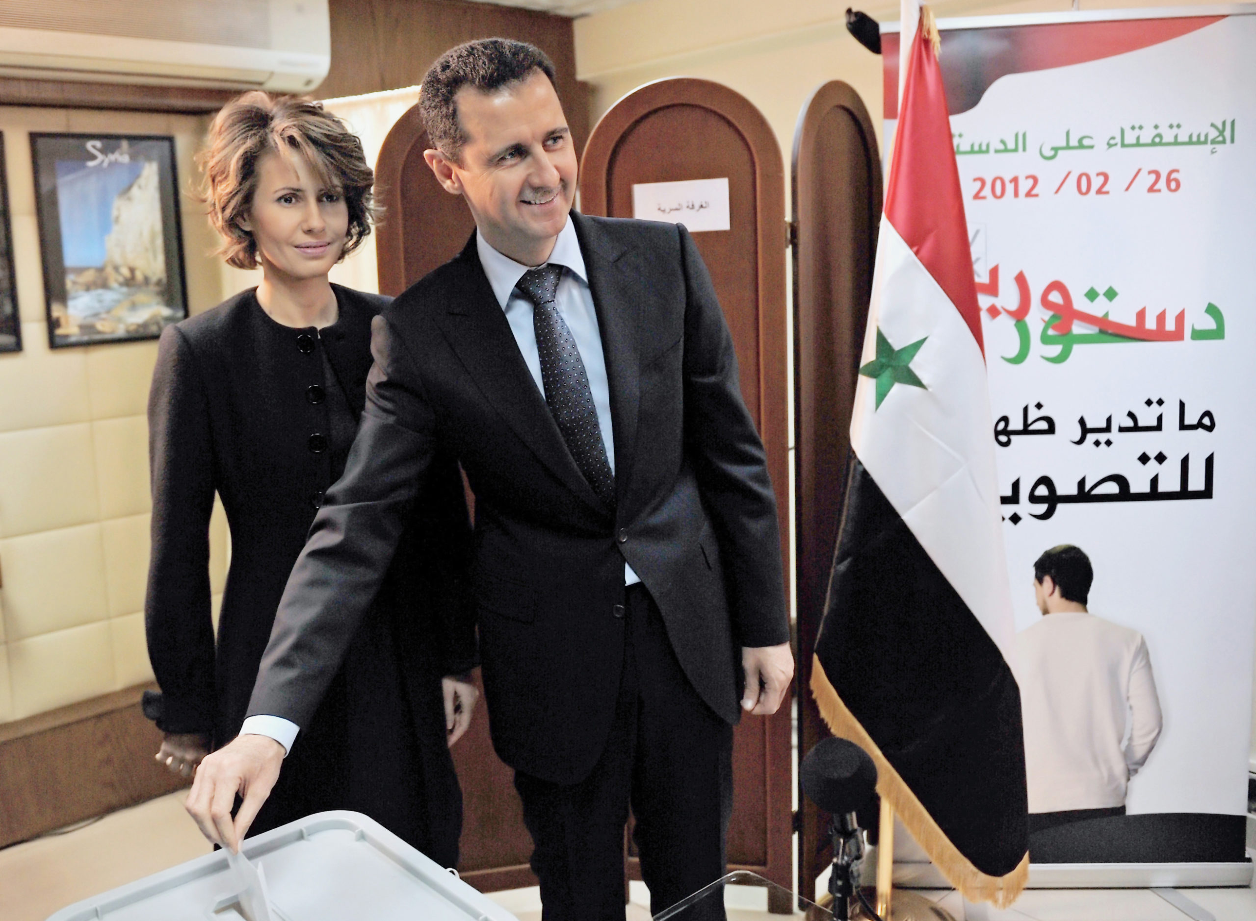 Syrian President Bashar Assad cats a ballot as his wife Asma looks on at a polling station in Damascus. (SANA/AFP via Getty Images)