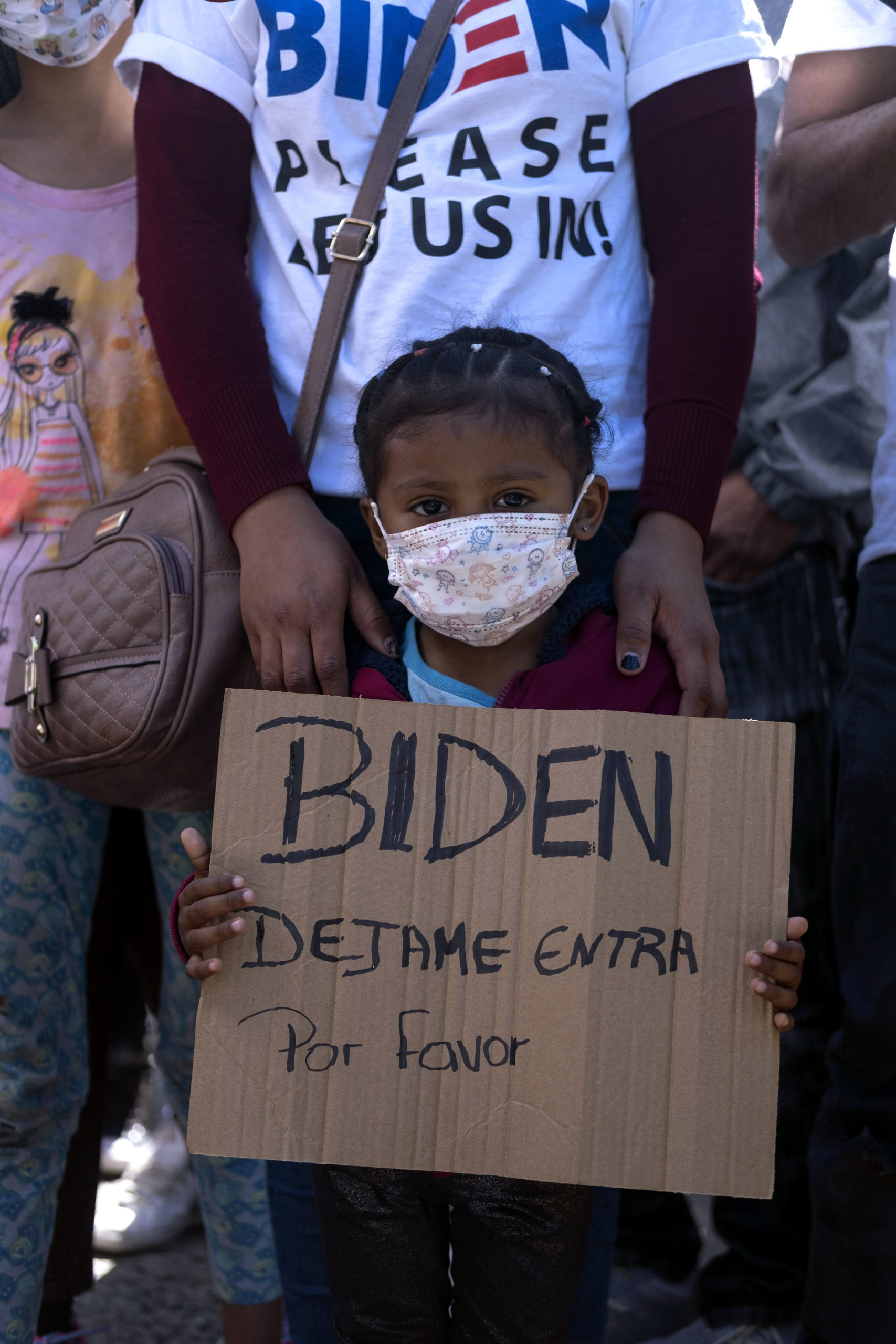 Dareli Matamoros, a girl from Honduras, holds a sign asking President Biden to let her in during a migrant demonstration demanding clearer United States migration policies, at San Ysidro crossing port in Tijuana, Baja California state, Mexico on March 2, 2021. - Thousands of migrants out of the Migrant Protection Protocol (MPP) program are stranded along the US-Mexico border without knowing when or how they will be able to start their migratory process with US authorities. (Photo by Guillermo Arias / AFP) (Photo by GUILLERMO ARIAS/AFP via Getty Images)