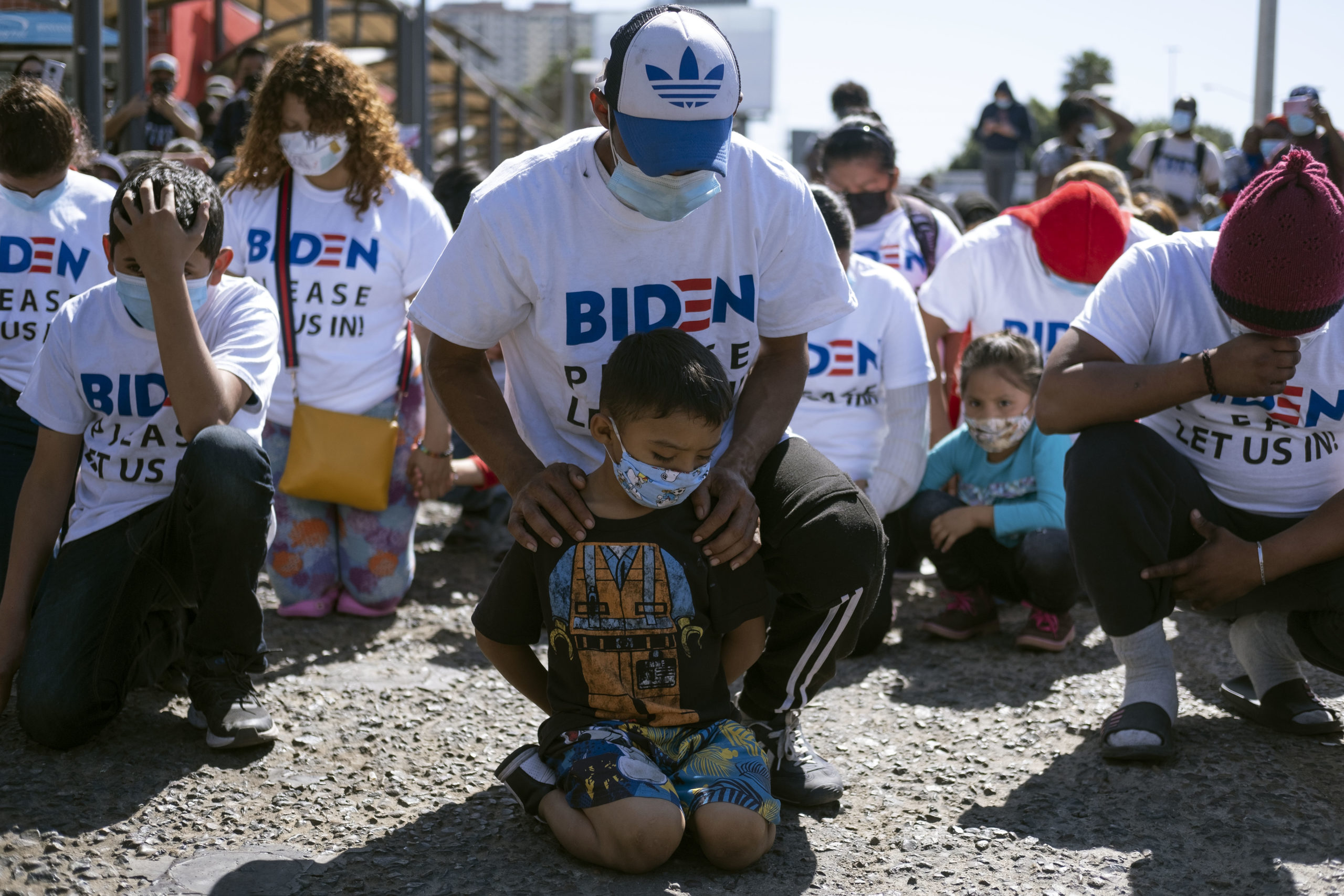 Yadiel Garcia and his father Fabricio, from Honduras, kneel as they pray during a migrant demonstration demanding clearer United States migration policies, at San Ysidro crossing port in Tijuana, Baja California state, Mexico on March 2, 2021. - Thousands of migrants out of the Migrant Protection Protocol (MPP) program are stranded along the US-Mexico border without knowing when or how they will be able to start their migratory process with US authorities. (Photo by Guillermo Arias / AFP) (Photo by GUILLERMO ARIAS/AFP via Getty Images)