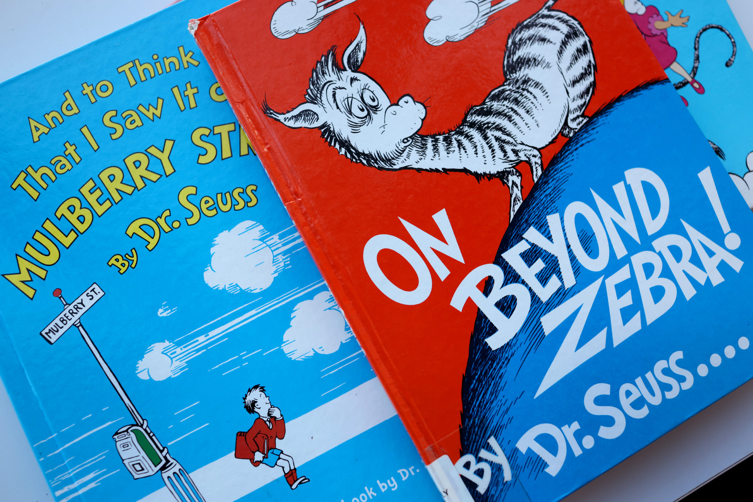 """CHICAGO, ILLINOIS - MARCH 02: Books by Theodor Seuss Geisel, aka Dr. Seuss, including """"On Beyond Zebra!"""" and """"And to Think That I Saw it on Mulberry Street,"""" are offered for loan at the Chinatown Branch of the Chicago Public Library on March 02, 2021 in Chicago, Illinois. The two titles are among six by the famed children's book author that will no longer be printed due to accusations of racist and insensitive imagery. The other titles include """"If I Ran the Zoo,"""" """"McElligot's Pool,"""" """"Scrambled Eggs Super!"""" and """"The Cat's Quizzer."""" (Photo Illustration by Scott Olson/Getty Images)"""