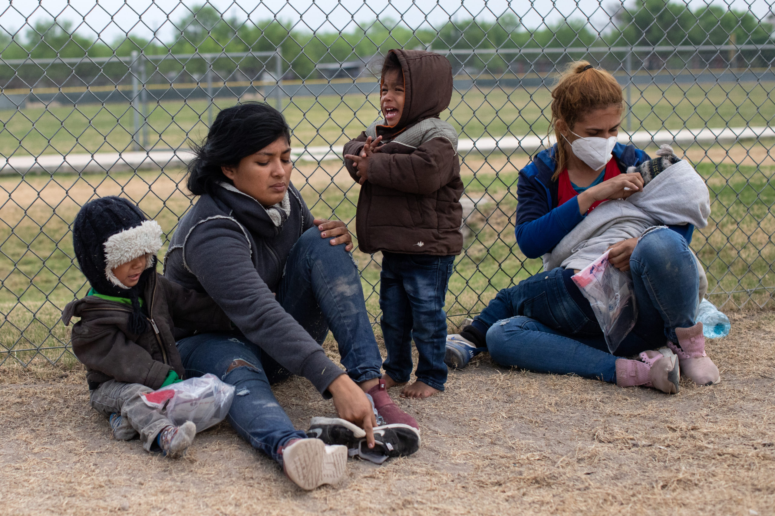 A child cried as illegal migrants waited on the grass near a public road as Customs and Border Protection officials worked to process and transport them to other facilities in La Joya, Texas on March 27, 2021. (Kaylee Greenlee - Daily Caller News Foundation)