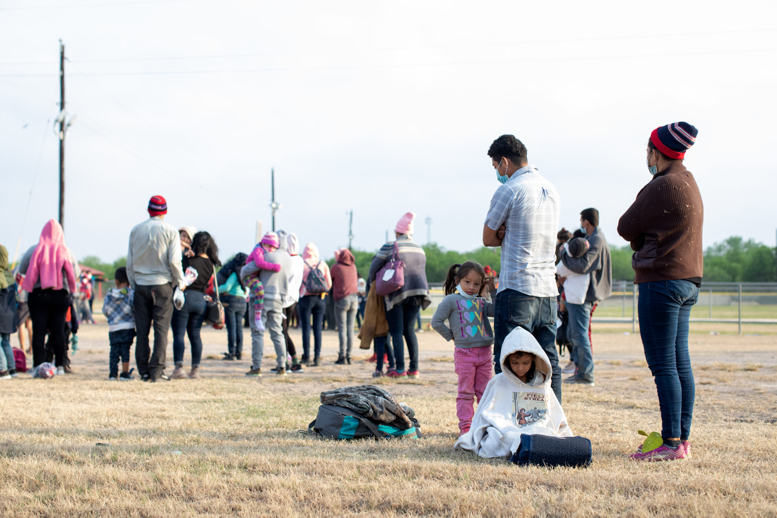 Illegal migrants wait on the side of a public road to be processed and taken to Customs and Border Protection facilities in La Joya, Texas on March 27, 2021. (Kaylee Greenlee - Daily Caller News Foundation)