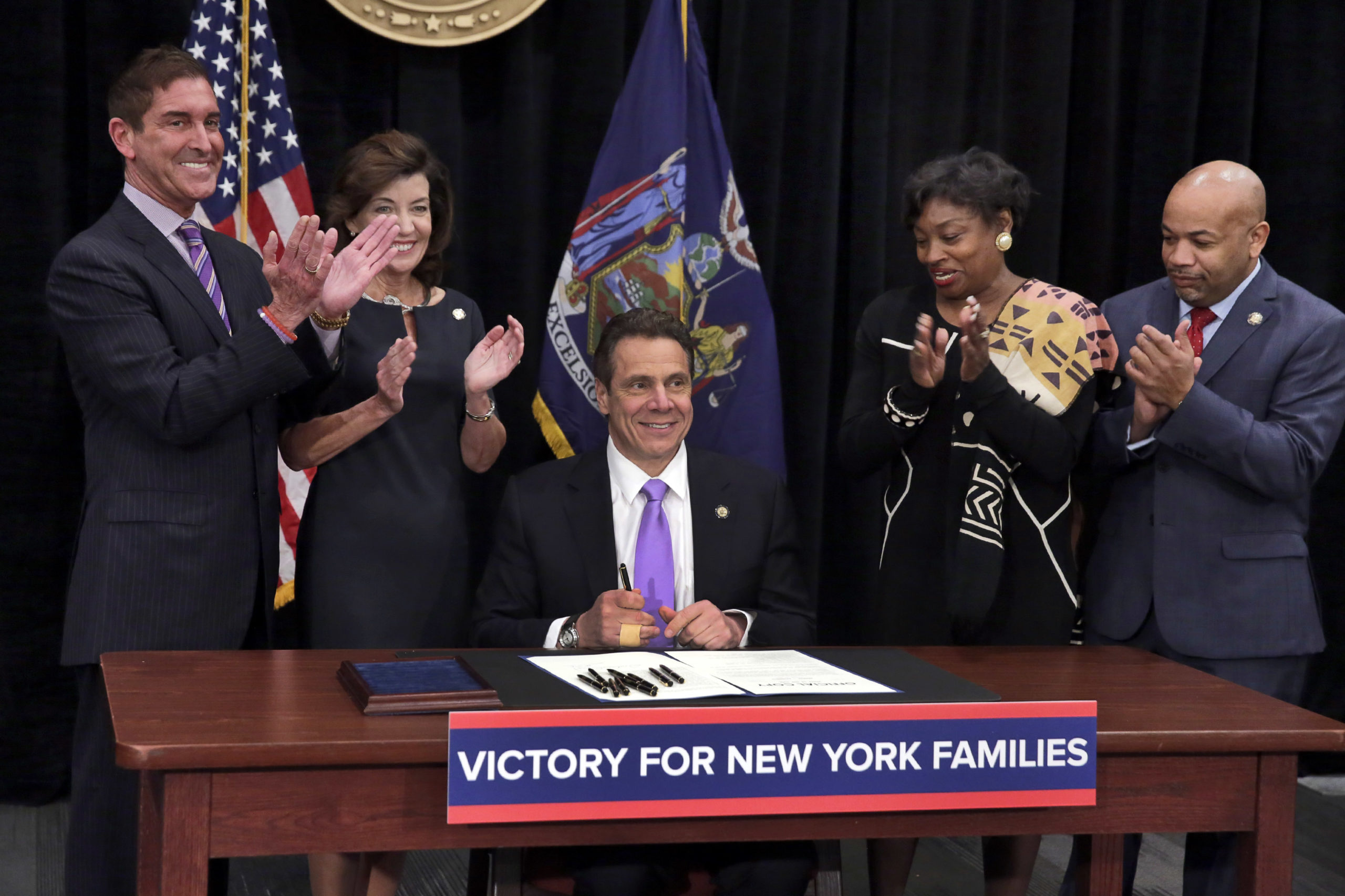 New York Gov. Andrew Cuomo, center, is applauded after he signed a law that will gradually raise New York's minimum wage to $15 on April 4, 2016. Standing, left to right, are New York state Sen. Jeffrey Klein, New York Lt. Gov. Kathy Hochul, New York state Sen. Andrea Stewart-Cousins, and New York state Assembly Speaker Carl Heastie. (Richard Drew-Pool/Getty Images)
