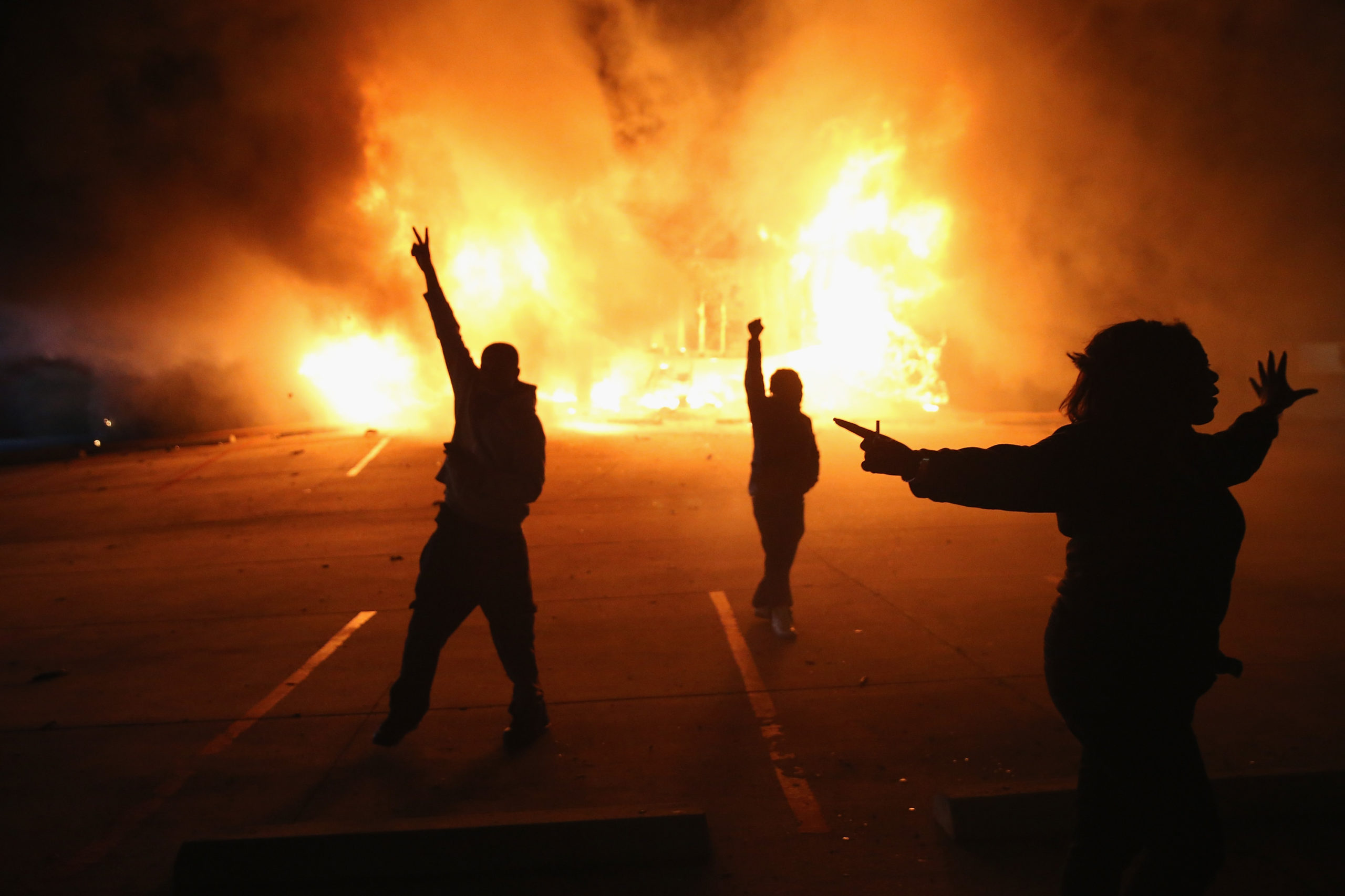 Demonstrators celebrate as a business burns after it was set on fire during rioting following the grand jury announcement in the Michael Brown case on November 24, 2014 in Ferguson, Missouri. (Photo by Scott Olson/Getty Images)