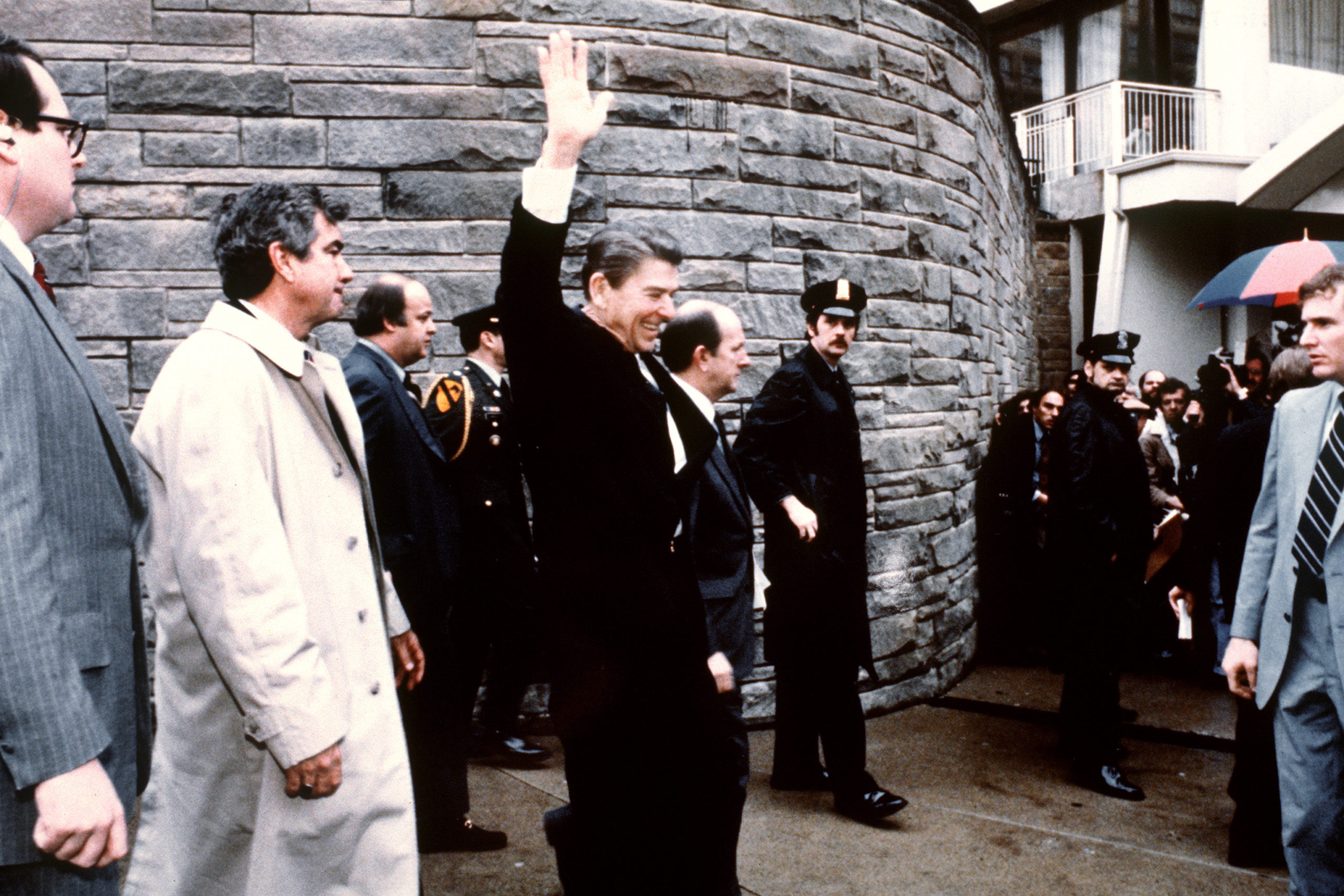 This photo taken by presidential photographer Mike Evens on March 30, 1981 shows President Ronald Reagan waving to the crowd just before the assassination attempt on him, after a conference outside the Hilton Hotel in Washington, D.C.. Reagan was hit by one of six shots fired by John Hinckley, who also seriously injured press secretary James Brady (just behind the car). (MIKE EVENS/AFP via Getty Images)