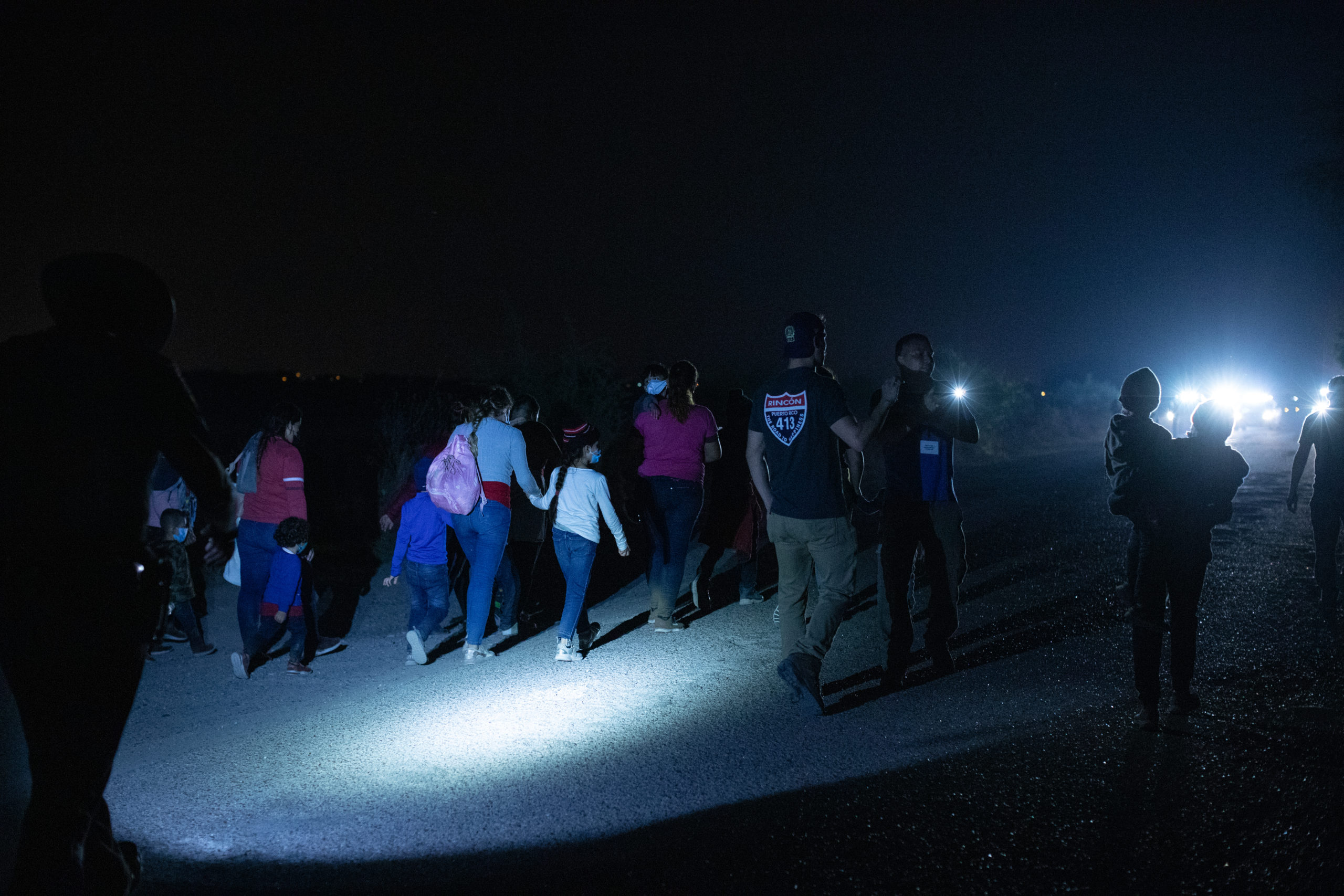 Illegal migrants wait on the side of a public road to be processed and taken to Customs and Border Protection facilities in La Joya, Texas on March 25, 2021. (Kaylee Greenlee - Daily Caller News Foundation)