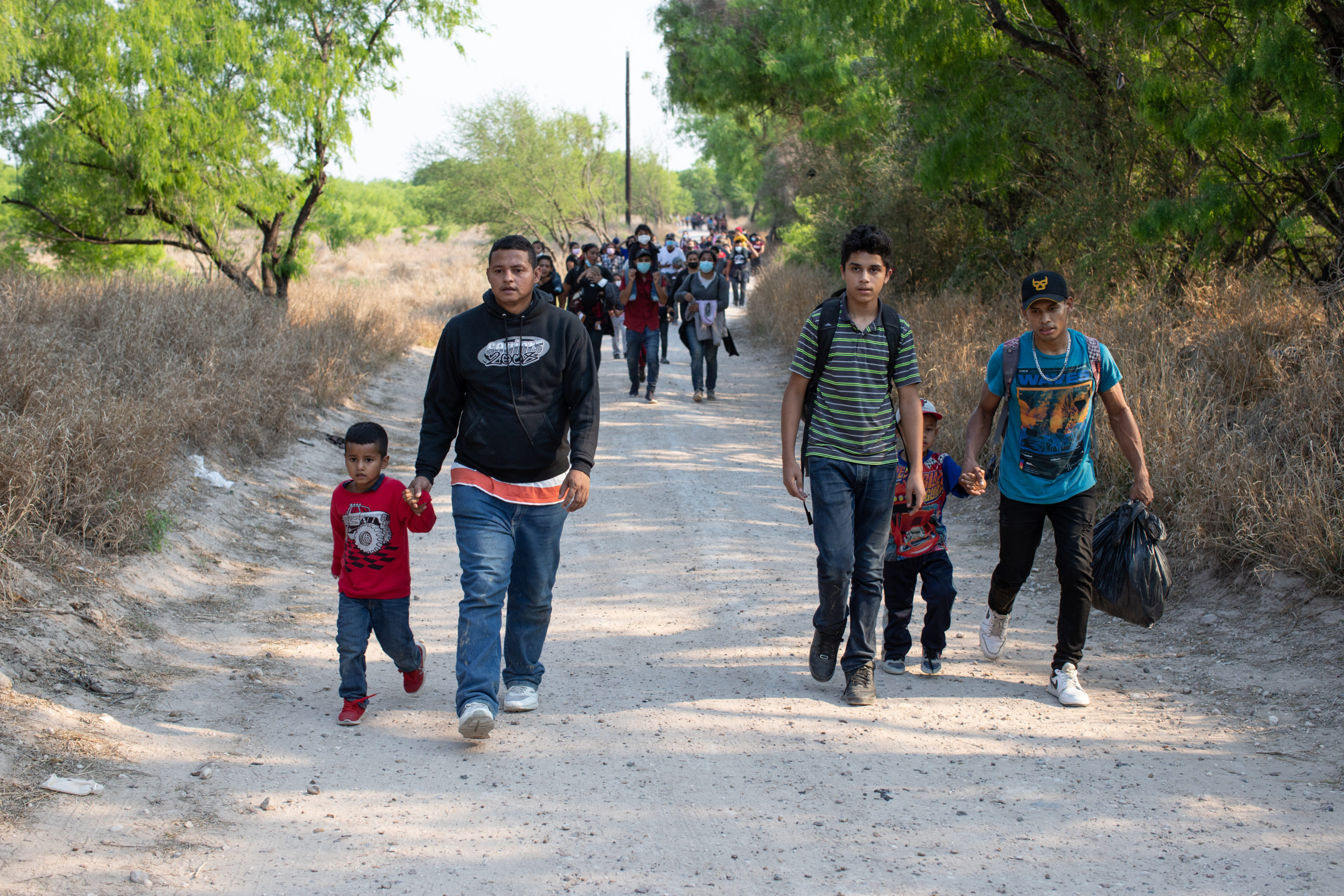 Illegal migrants cross through private land on their way to a Customs and Border Protection processing facility near Mission, Texas on March 25, 2021. (Kaylee Greenlee - Daily Caller News Foundation)