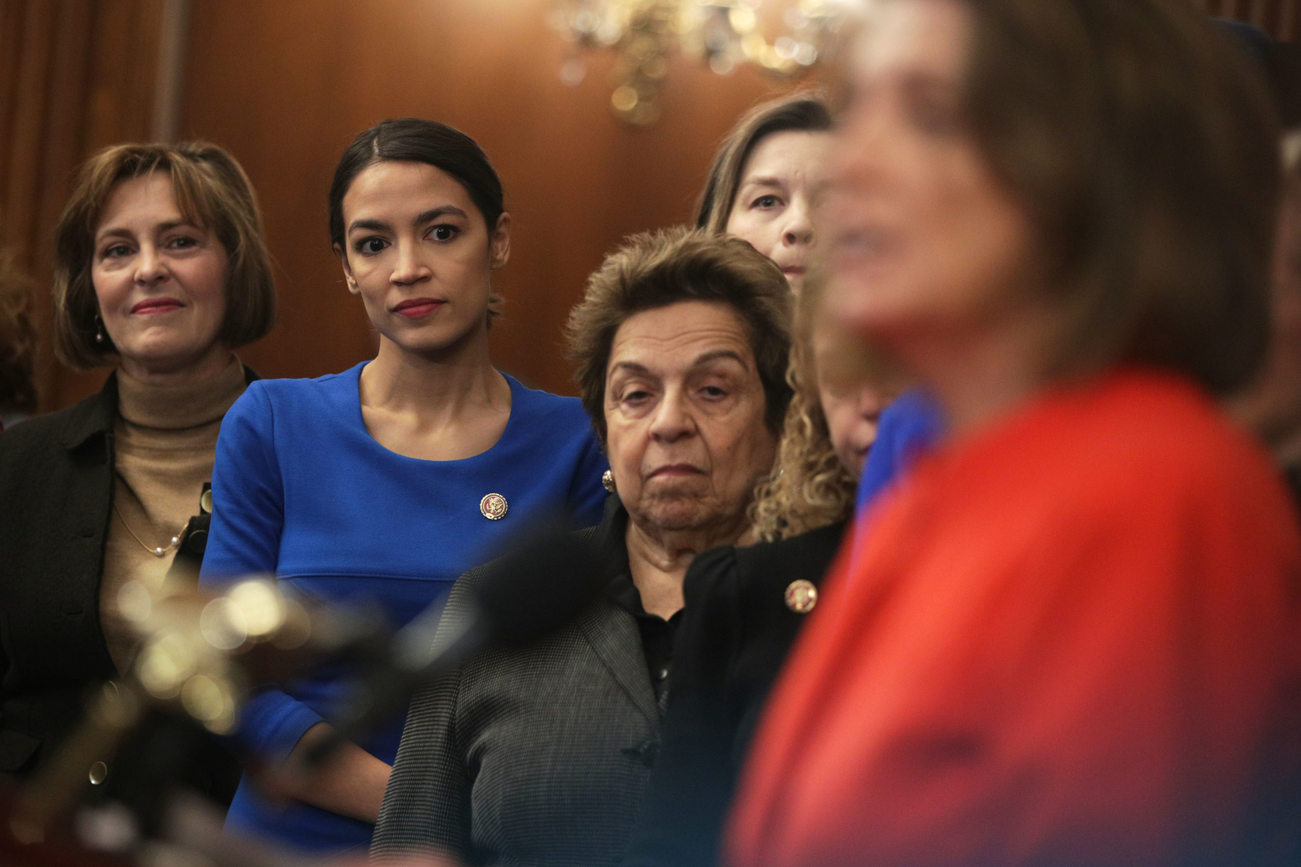 """WASHINGTON, DC - JANUARY 30: (L-R) U.S. Rep. Kathy Castor (D-FL), Rep. Alexandria Ocasio-Cortez (D-NY), and Rep. Donna Shalala (D-FL) listen as Speaker of the House Rep. Nancy Pelosi (D-CA) speaks during a news conference at the U.S. Capitol January 30, 2019 in Washington, DC. House Democrats held a news conference to introduce the """"Paycheck Fairness Act."""" (Photo by Alex Wong/Getty Images)"""