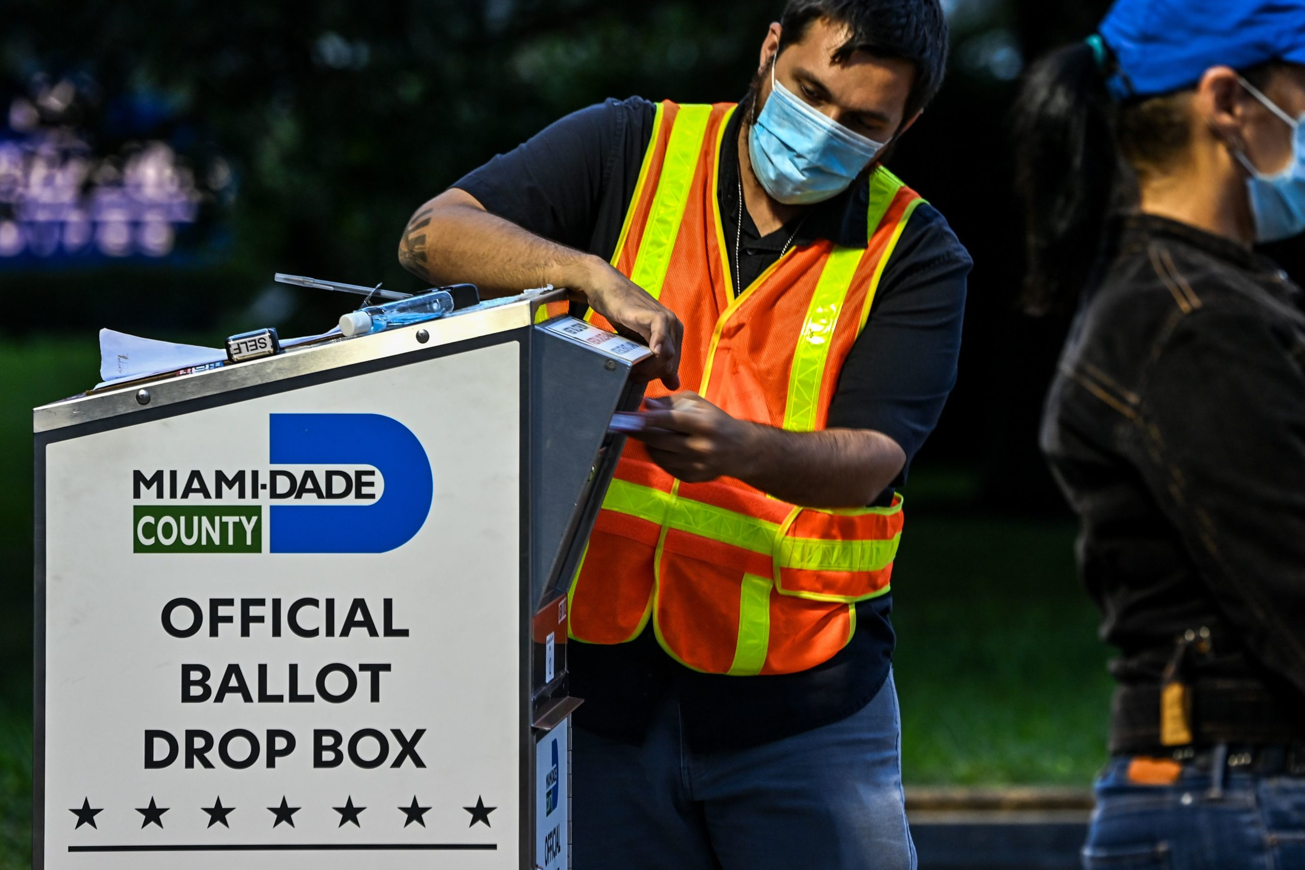 A poll worker helps a voter as she drops off her mail-in ballot at an official Miami-Dade County drive-thru ballot drop box in Miami, Florida on Nov. 3. (Chandan Khanna/AFP via Getty Images)
