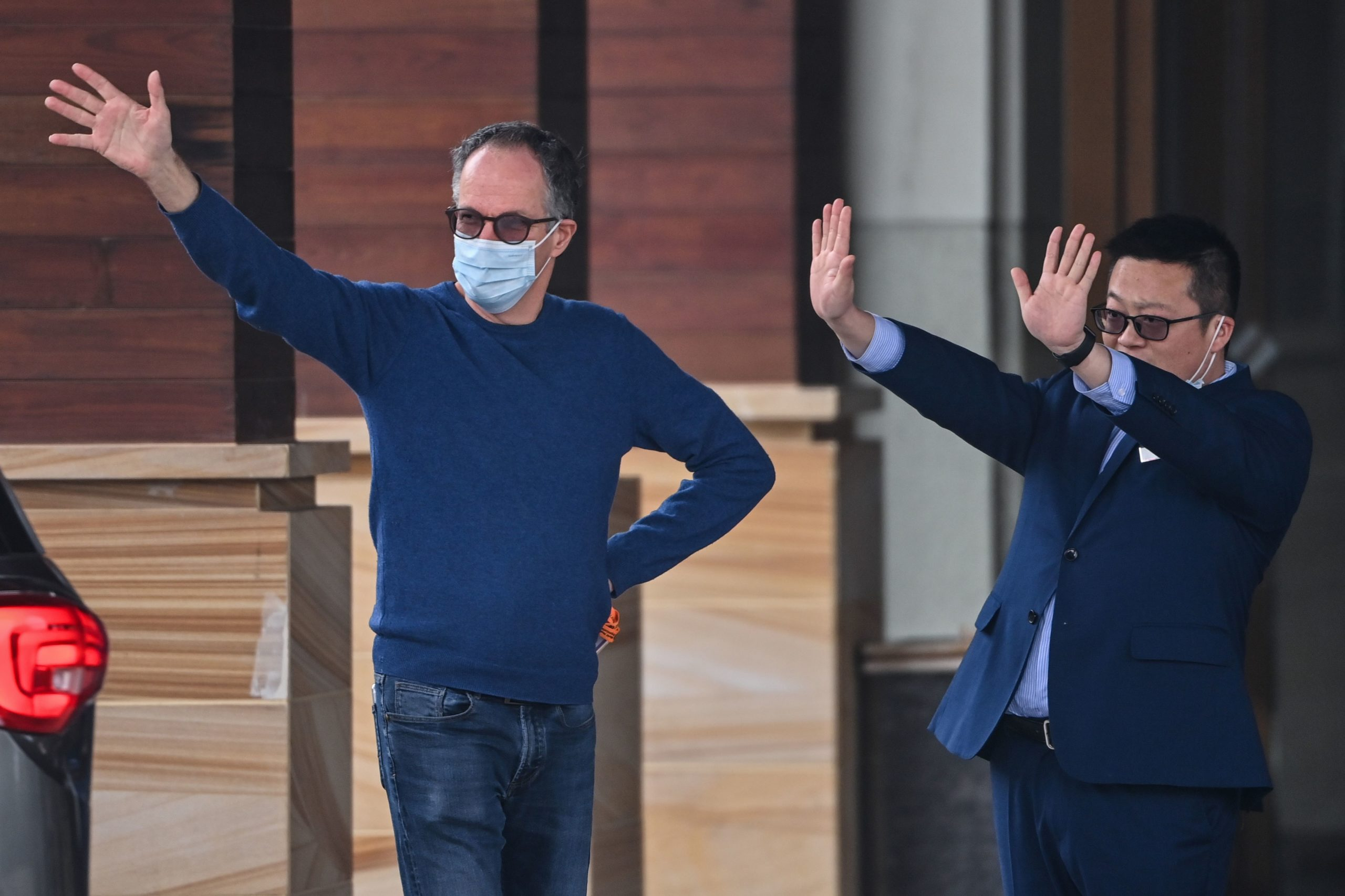 WHO team member Peter Ben Embarek (L) waves as group members Marion Koopmans and Peter Daszak leave their hotel after the World Health Organization (WHO) team wrapped up its investigation into the origins of the COVID-19 coronavirus in Wuhan in China's central Hubei province on February 10, 2021. (HECTOR RETAMAL/AFP via Getty Images)