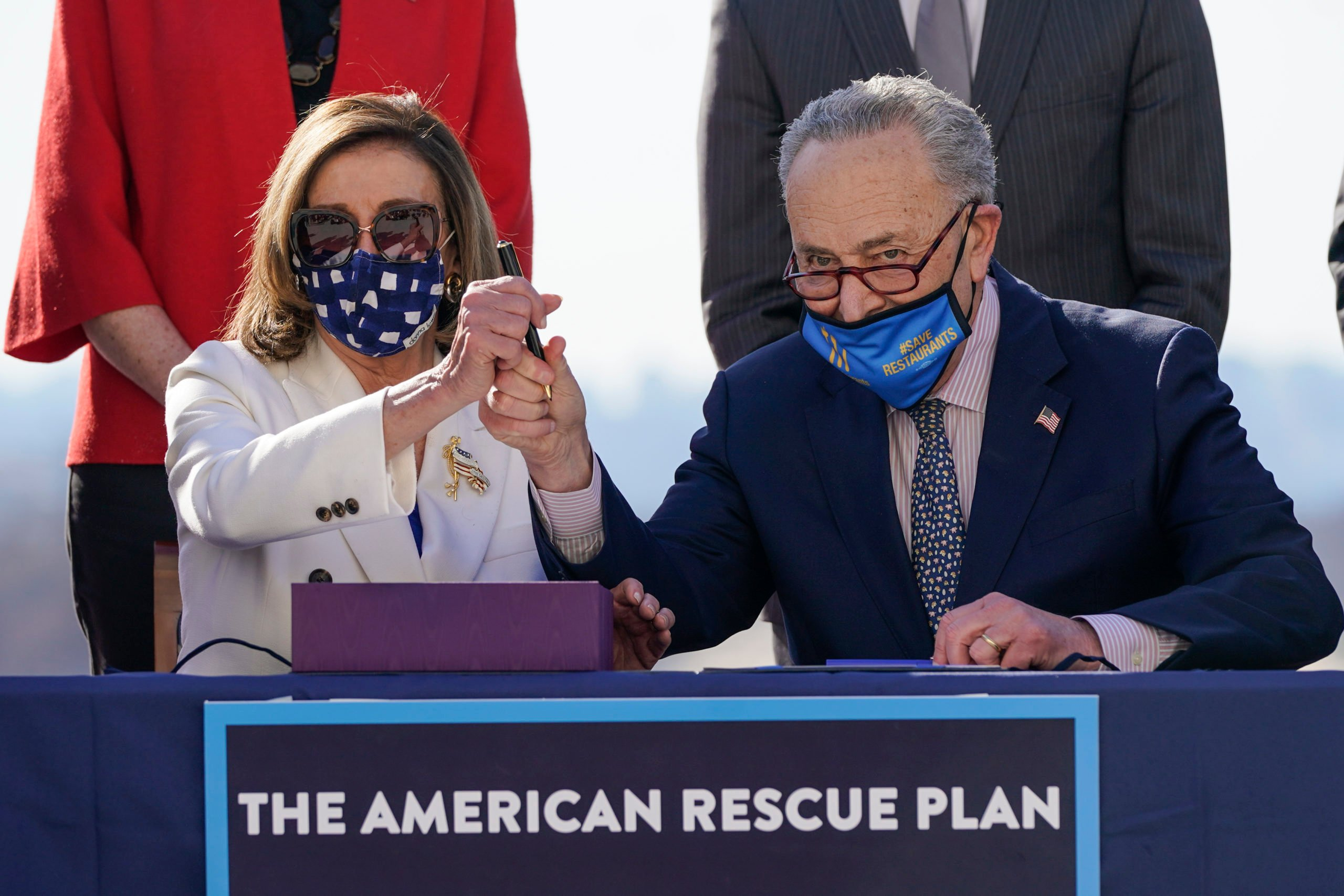 Speaker of the House Nancy Pelosi and Senate Majority Leader Chuck Schumer sign the $1.9 trillion coronavirus relief bill in March. (Drew Angerer/Getty Images)
