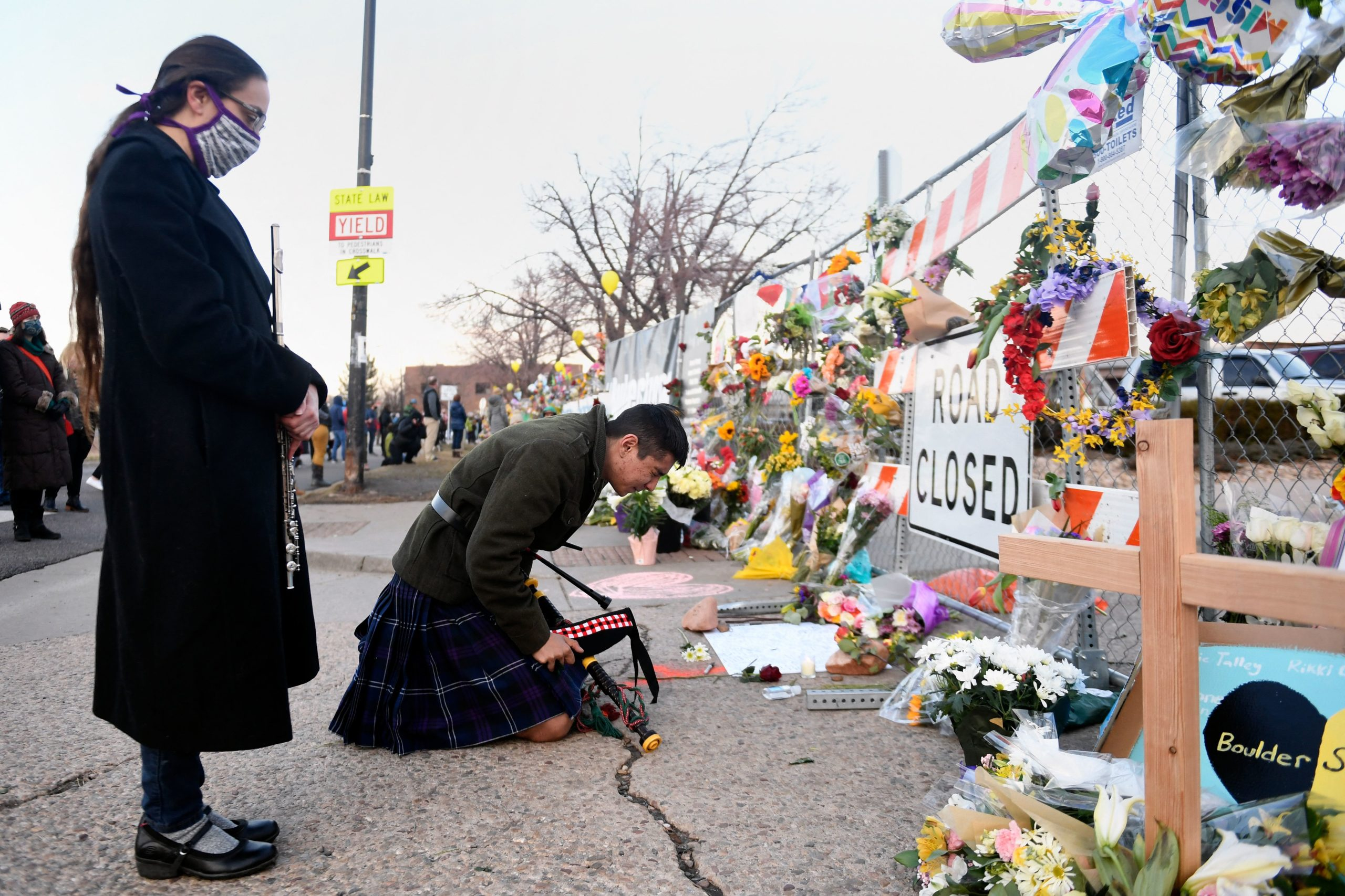 Geoffrey Nicosia (R) and Nikki Guillory reflect after playing music outside of a King Soopers grocery store in Boulder, Colorado on March 24, 2021, to honor the ten people killed during a mass shooting three days prior. (JASON CONNOLLY/AFP via Getty Images)
