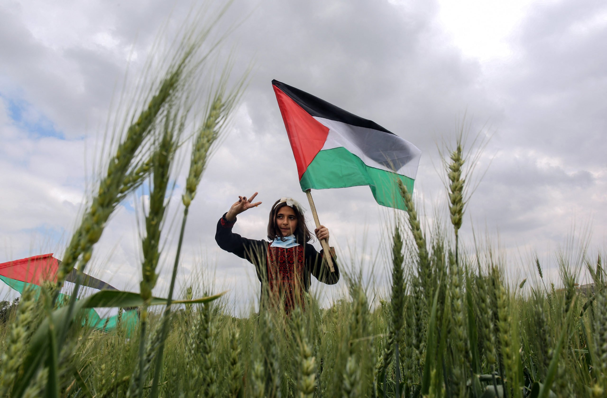 A Palestinian girl waves her national flag during an event marking Land Day near the Israel-Gaza border, east of Khan Yunis town in the Southern Gaza Strip on March 30, 2021. - Palestinians commemorate on March 30 the Land Day's annual demonstrations, marking the deaths of six Arab Israeli protesters at the hands of Israeli police and troops during mass protests in 1976 against plans to confiscate Arab land in the northern Galilee region. (Photo by SAID KHATIB / AFP) (Photo by SAID KHATIB/AFP via Getty Images)