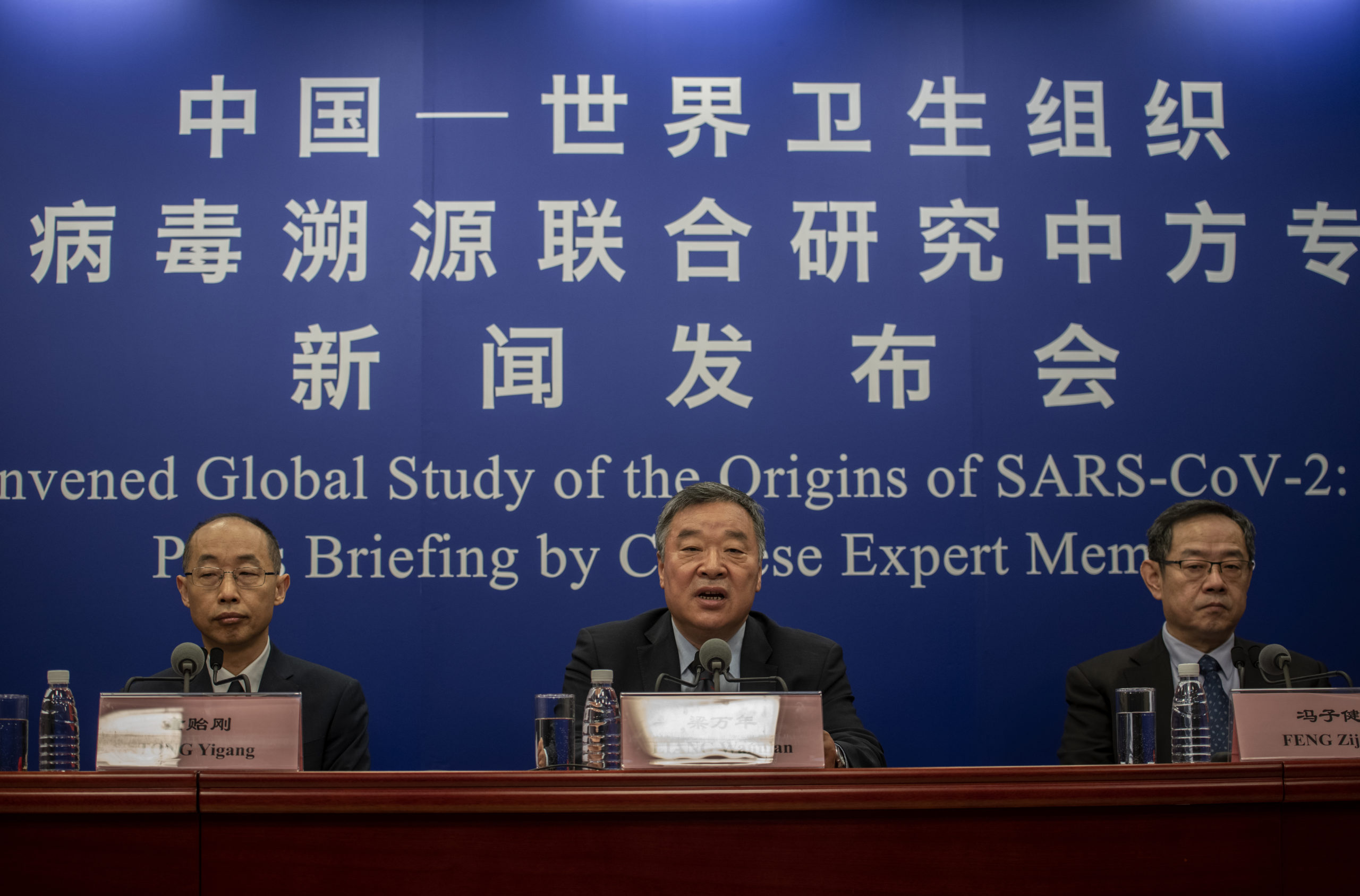 BEIJING, CHINA - MARCH 31: Head of the Expert Group on Covid Response at China's National Health Commission Liang Wannian, center, answers a question as Tong Yigang, left, and Feng Zijian, right, listen during a press conference addressing the World Health Organization (WHO) report on the origins of SARS-CoV-2, at the National Health Committee on March 31, 2021 in Beijing, China. (Kevin Frayer/Getty Images)