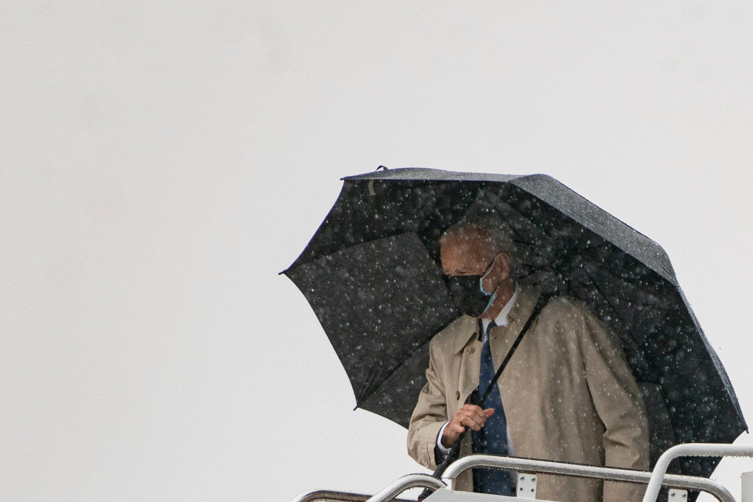 """US President Joe Biden boards Air Force One in the rain at Andrews Air Force Base on March 31, 2021 in Maryland. - US President Joe Biden is traveling to Pittsburgh, Pennsylvania to deliver remarks on his economic vision for the future and the Biden-Harris administration's plan to """"Build Back Better"""" for the American people. (Photo by ALEX EDELMAN/AFP via Getty Images)"""
