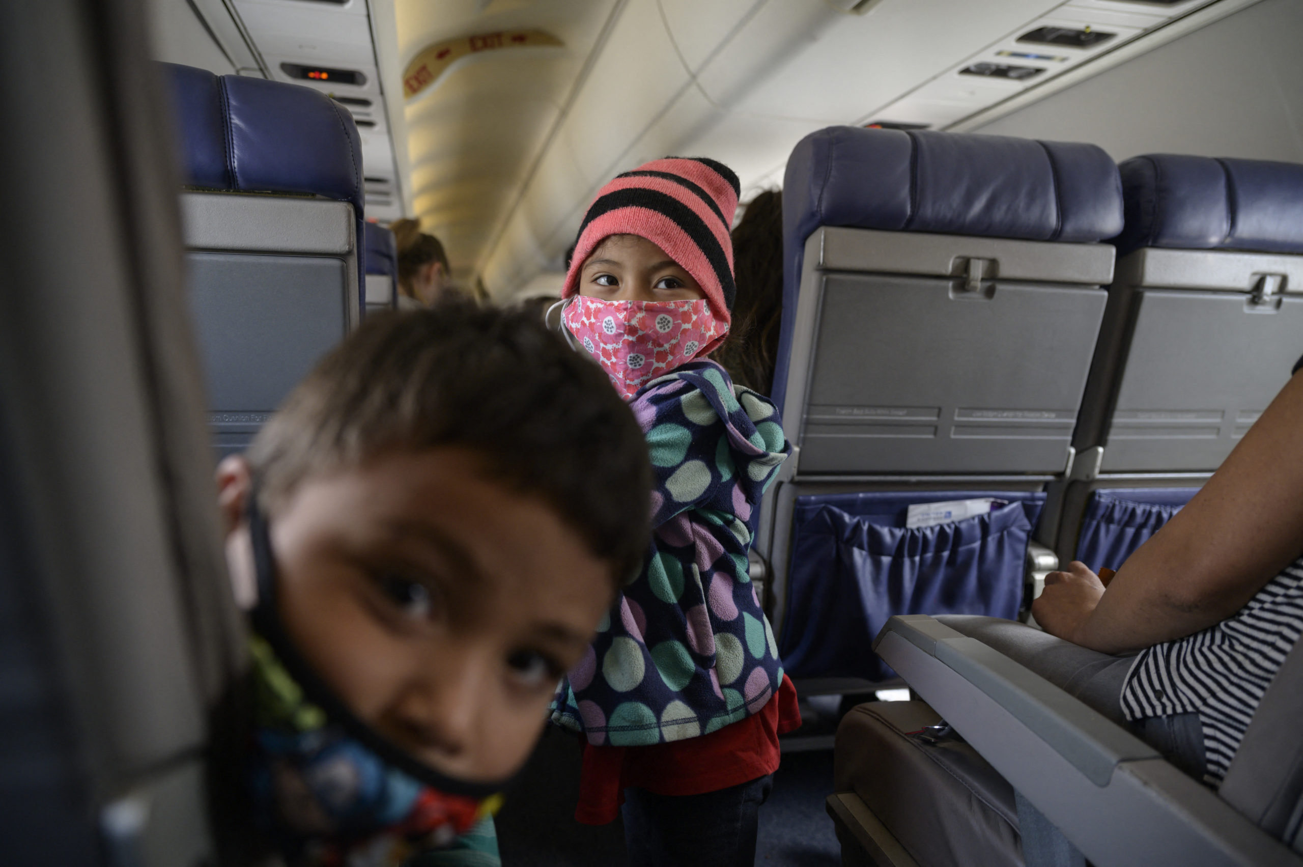 Siblings Dariel (L) and Diana (C) from El Salvador travel on a flight on March 30, 2021 from McAllen to Houston following their release from a US government holding facility for illegal migrants seeking asylum in McAllen, Texas.. (Photo by Ed JONES / AFP) (Photo by ED JONES/AFP via Getty Images)