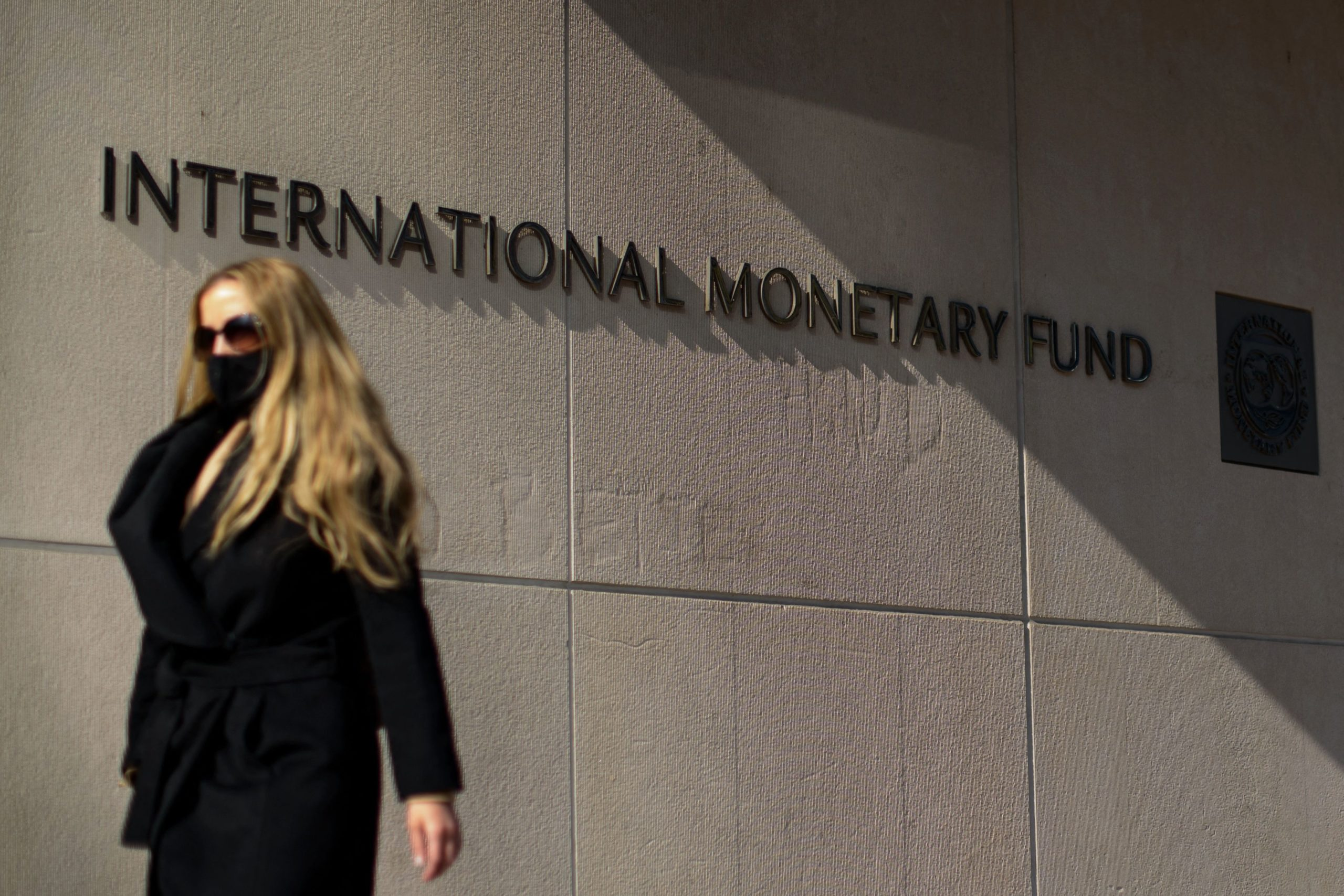 A woman walks past an International Monetary Fund headquarters building in Washington, D.C. on Monday. (Mandel Ngan/AFP via Getty Images)