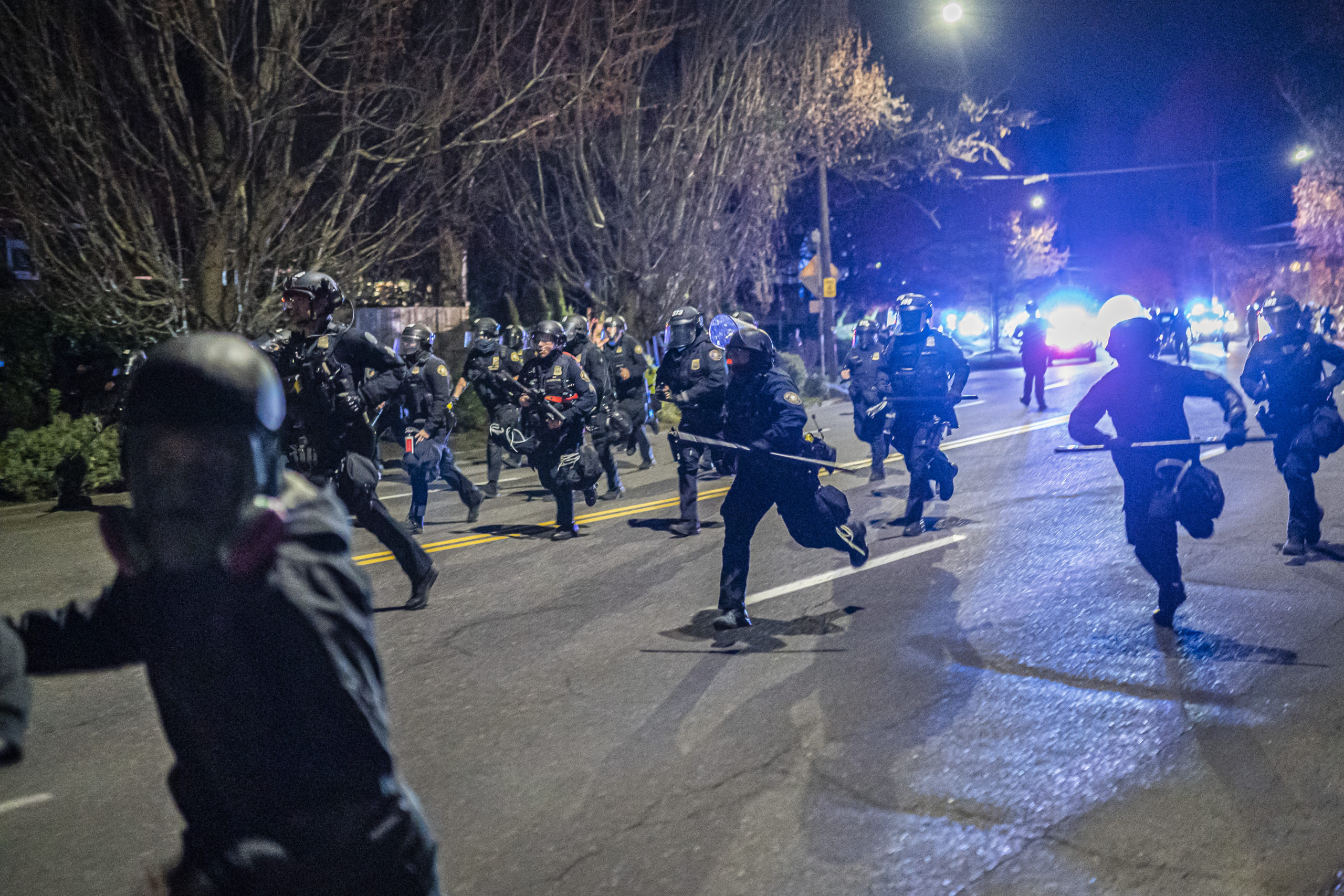 Portland police officers chase demonstrators after a riot was declared during a protest on April 12 in Portland, Oregon. (Nathan Howard/Getty Images)