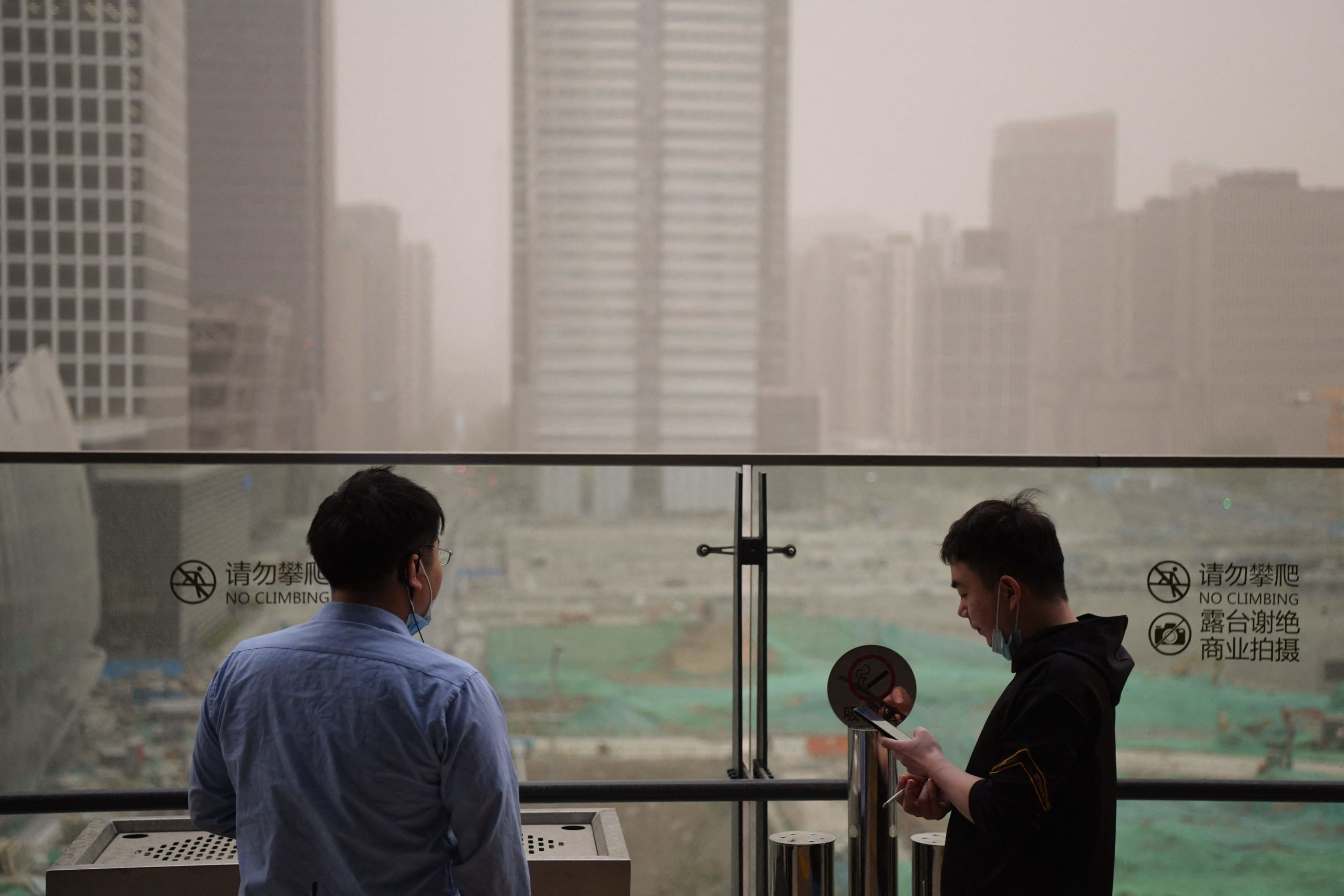 Two men smoke cigarettes in the central business district during a sandstorm in Beijing on April 15, 2021. (Photo by Greg Baker/AFP via Getty Images)