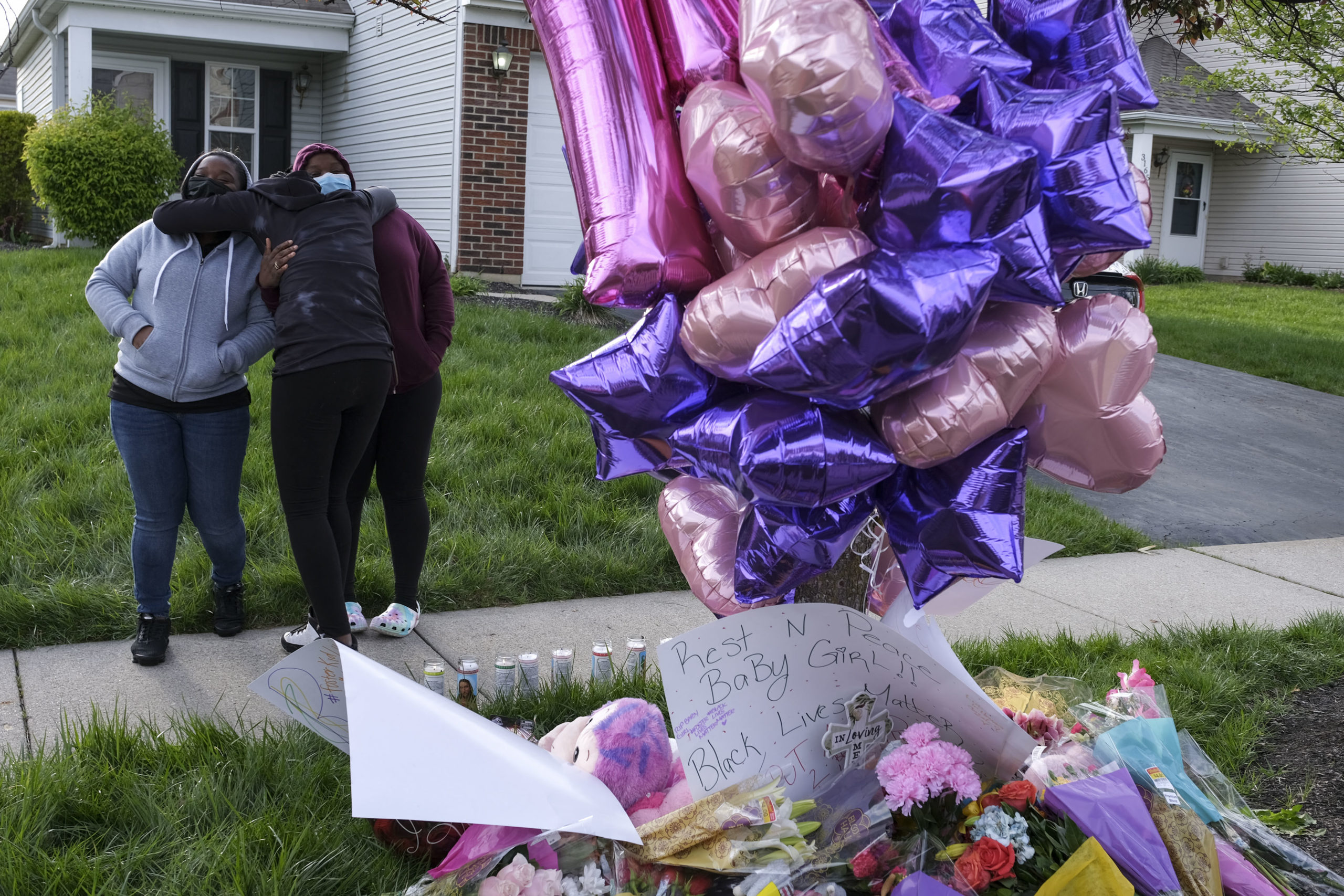 People gather around a pop-up memorial at the site where a Columbus Police Department officer shot and killed Ma'Khia Bryant, 16, in Columbus, Ohio on April 21, 2021. - Police in the US state of Ohio fatally shot a Black teenager who appeared to be lunging at another person with a knife, less than an hour before former officer Derek Chauvin was convicted of murdering George Floyd. The shooting occurred at a tense time with growing outrage against racial injustice and police brutality in the United States, and set off protests in the city of Columbus. (Photo by Jeff Dean / AFP) (Photo by JEFF DEAN/AFP via Getty Images)