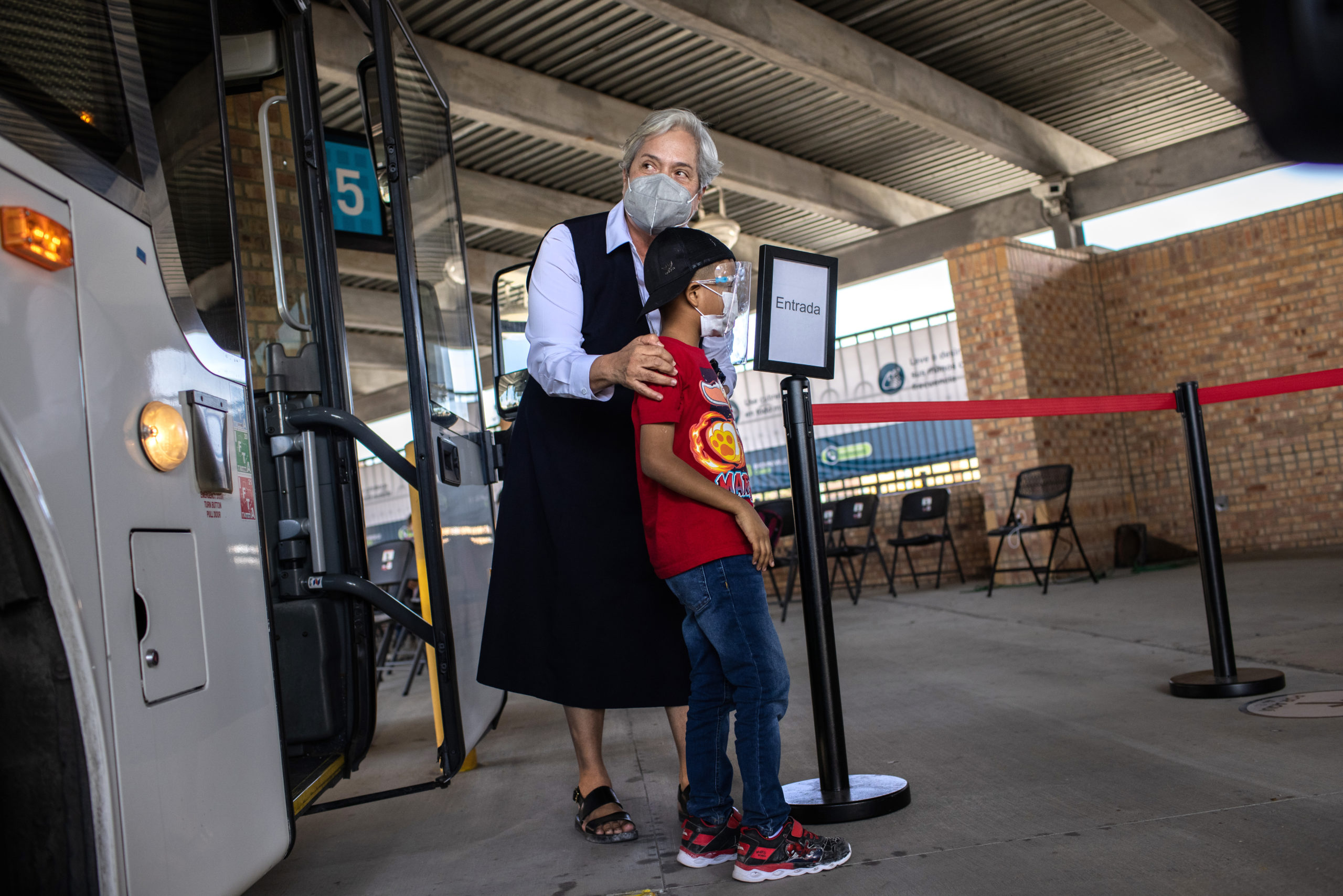 BROWNSVILLE, TEXAS - FEBRUARY 26: Sister Norma Pimentel, Executive Director of Catholic Charities of the Rio Grande Valley escorts a young asylum seeker upon his entry into the United States on February 26, 2021 in Brownsville, Texas. Her group was one of the first to cross into south Texas as part of the Biden administration's unwinding of the Trump-era Migrant Protection Protocols, (MPP), also known as the 'Remain in Mexico' immigration policy. Many of the asylum seekers had been waiting in the squalid camp alongside the Rio Grande in Matamoros for more than a year and became close to camp logistics workers, many of them American. The immigrants are now free to travel to destinations within the United States pending asylum court hearings. (Photo by John Moore/Getty Images)