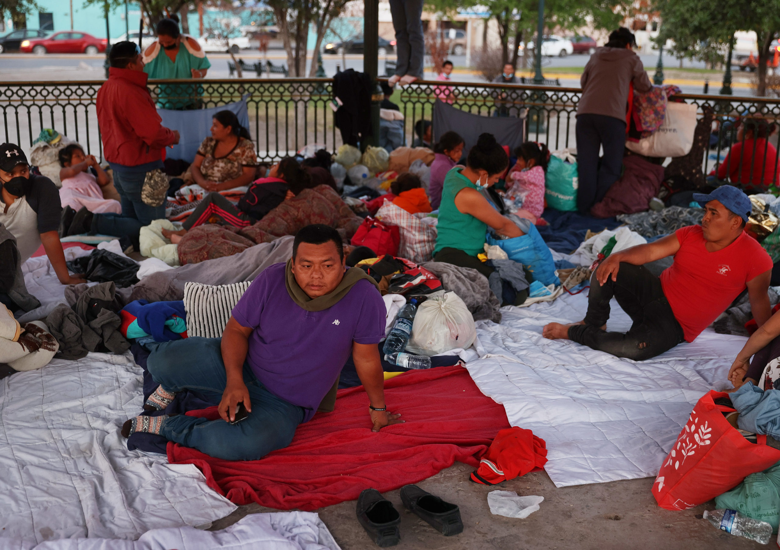 REYNOSA, MEXICO - MARCH 25: Emner, originally from Guatemala, sits with other migrants camping in the Plaza las Americas after being deported when they were caught crossing illegally into the United States on March 25, 2021 in Reynosa, Mexico. Emner says he had been waiting in the park for eight days hoping for a chance to seek asylum in the United States. (Photo by Joe Raedle/Getty Images)