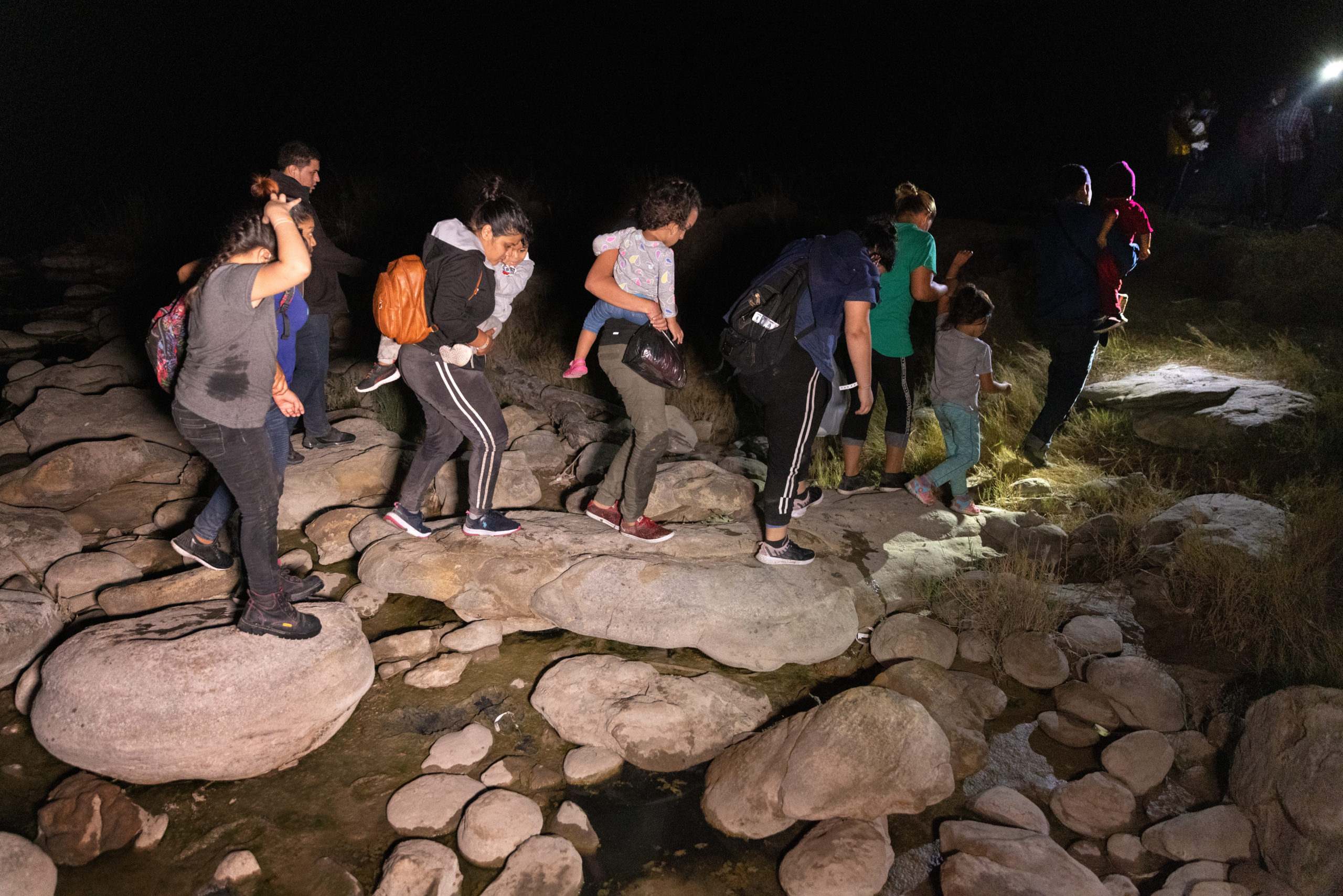 Immigrants walk from the bank of the Rio Grande after being smuggled across the U.S.-Mexico border on April 14, 2021 in Roma, Texas. (John Moore/Getty Images)