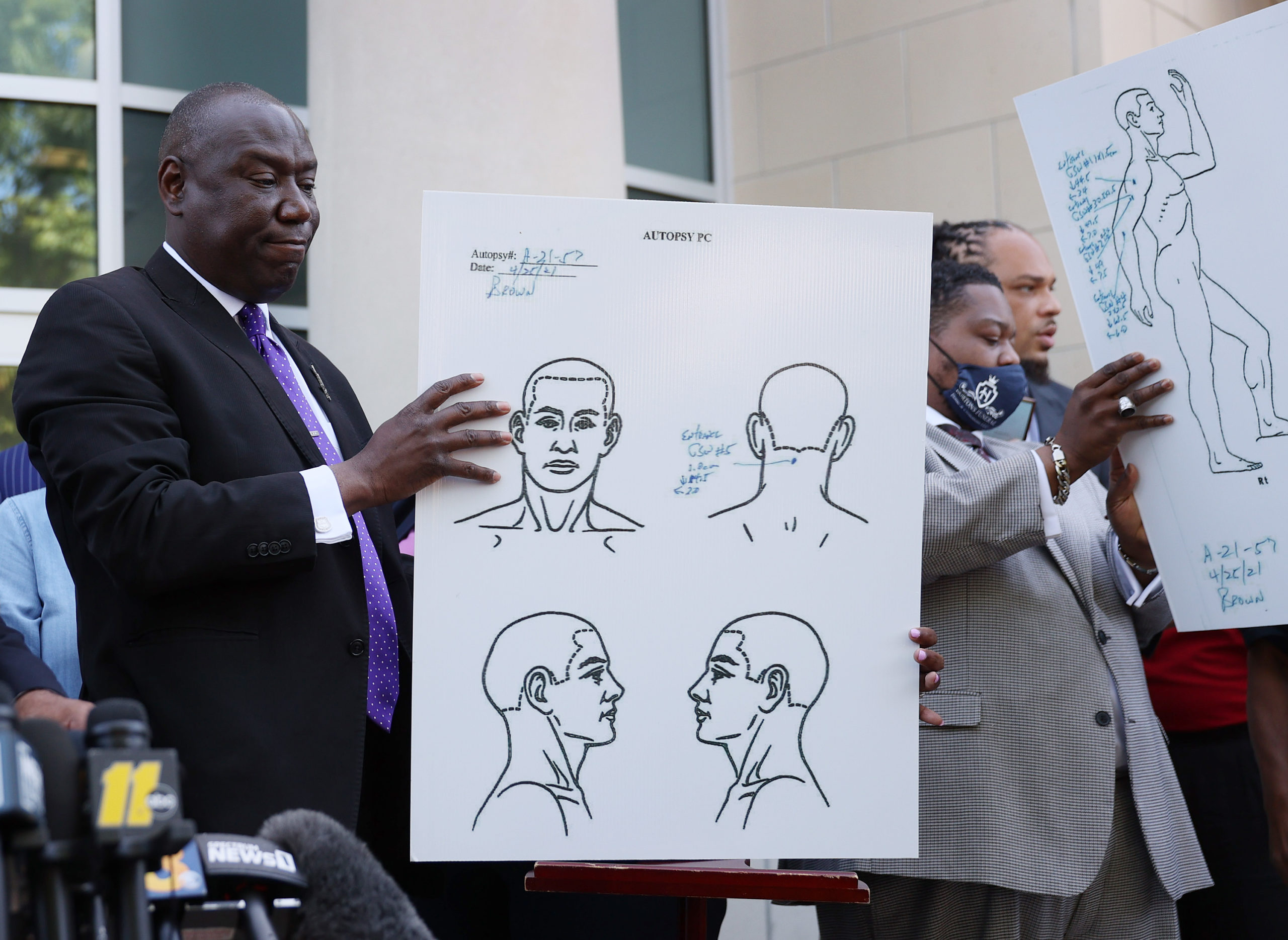 Benjamin Crump (L), one of the lawyers representing the family of Andrew Brown Jr., holds an autopsy chart that his team conducted showing where Mr. Brown was shot on April 27, 2021 in Elizabeth City, North Carolina. Mr. Crump and family members spoke to the media about the 20 seconds of police body camera footage they were shown and an autopsy they performed after the shooting death of Andrew Brown Jr. on April 21 by Pasquotank County Sheriff deputies. (Photo by Joe Raedle/Getty Images)