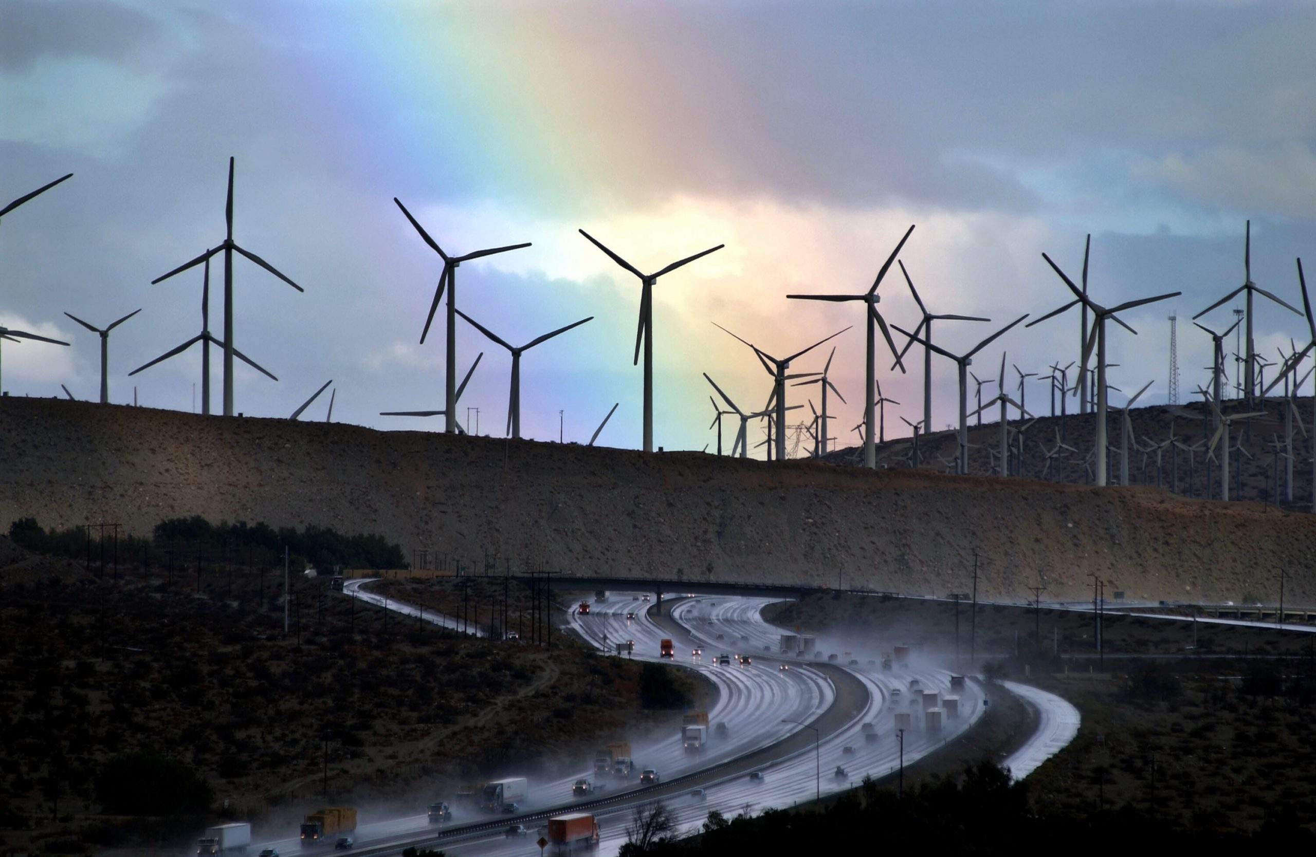 PALM SPRINGS, CA - DECEMBER 17: A rainbow forms behind giant windmills near rain-soaked Interstate 10 as an El Nino-influenced storm passes over the state on December 17, 2002 near Palm Springs, California. Because of consistantly high winds, thousands of giant windmills have sprouted in the area to create wind-powered electricity. (Photo by David McNew/Getty Images)