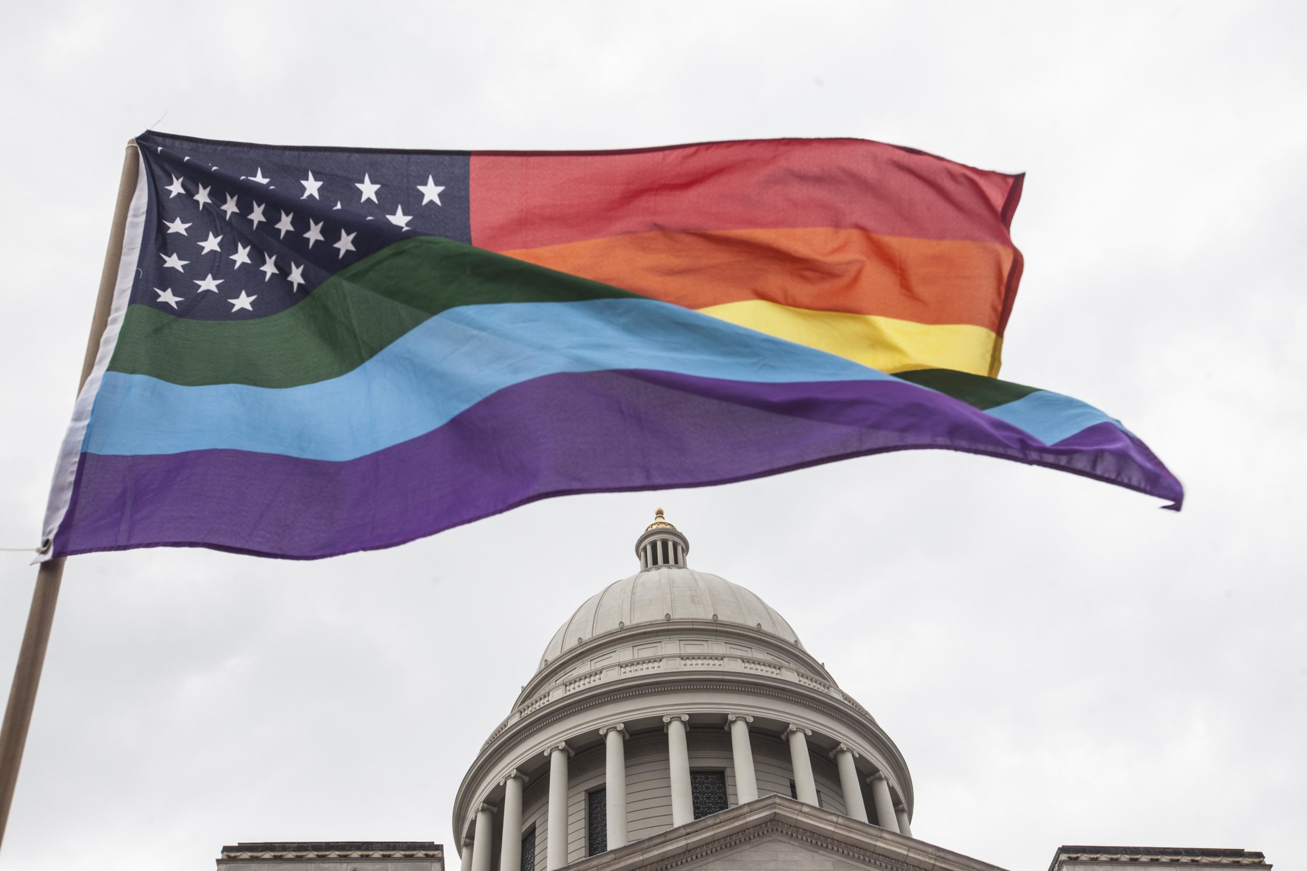 """LITTLE ROCK, AR - APRIL 1: A rainbow flag flies over the crowd during a press conference by the Human Rights Campaign on the steps of the Arkansas State Capital in Little Rock following Gov. Asa Hutchinson's comments on House Bill 1228, a bill passed which prohibits state and local governments from infringing on a person's religious beliefs without a """"compelling"""" interest, on April 1, 2015 in Little Rock, Arkansas. (Photo by Andrea Morales/Getty Images)"""