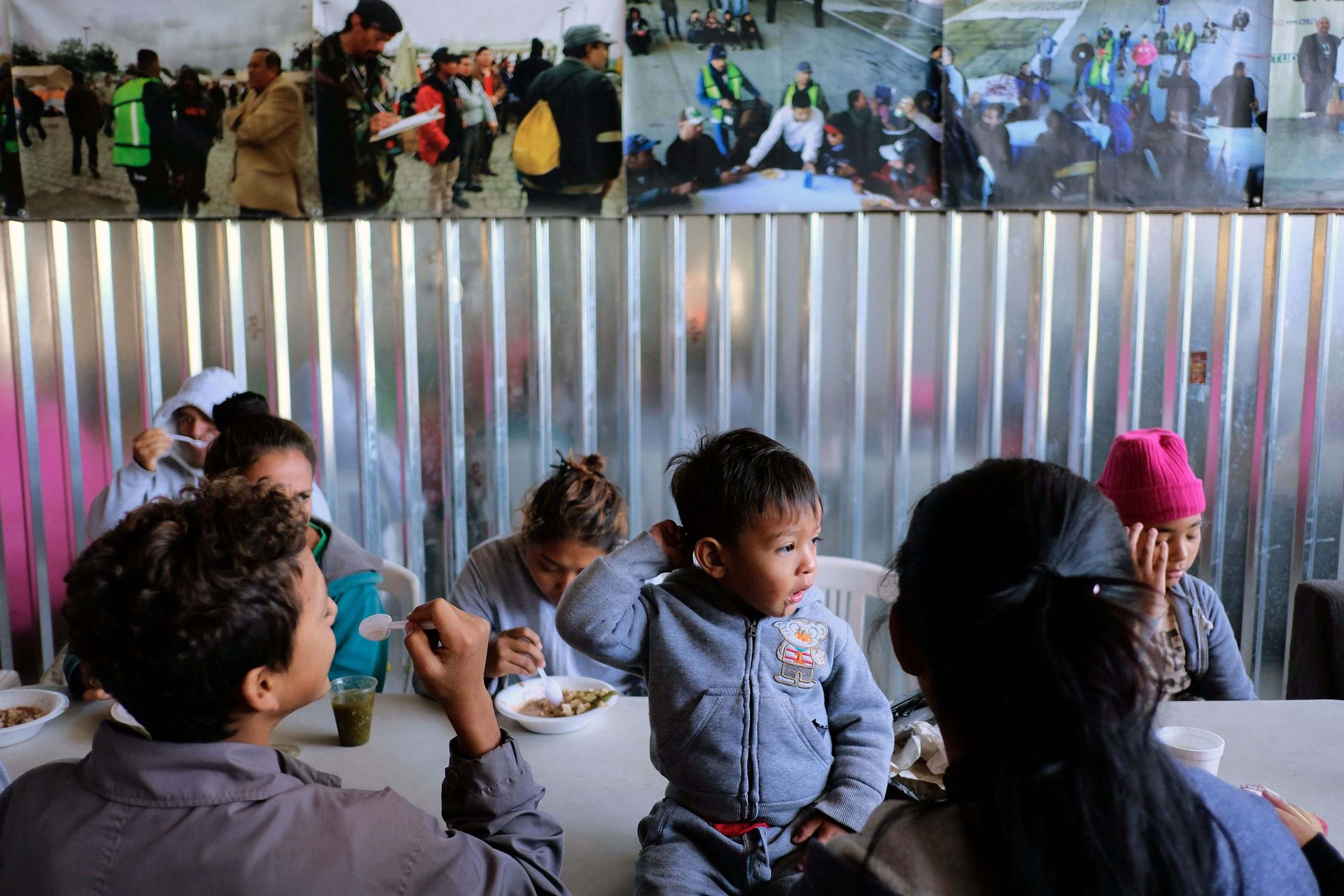 Christian (C) sits next to his mother (R) and other Central American migrants during the