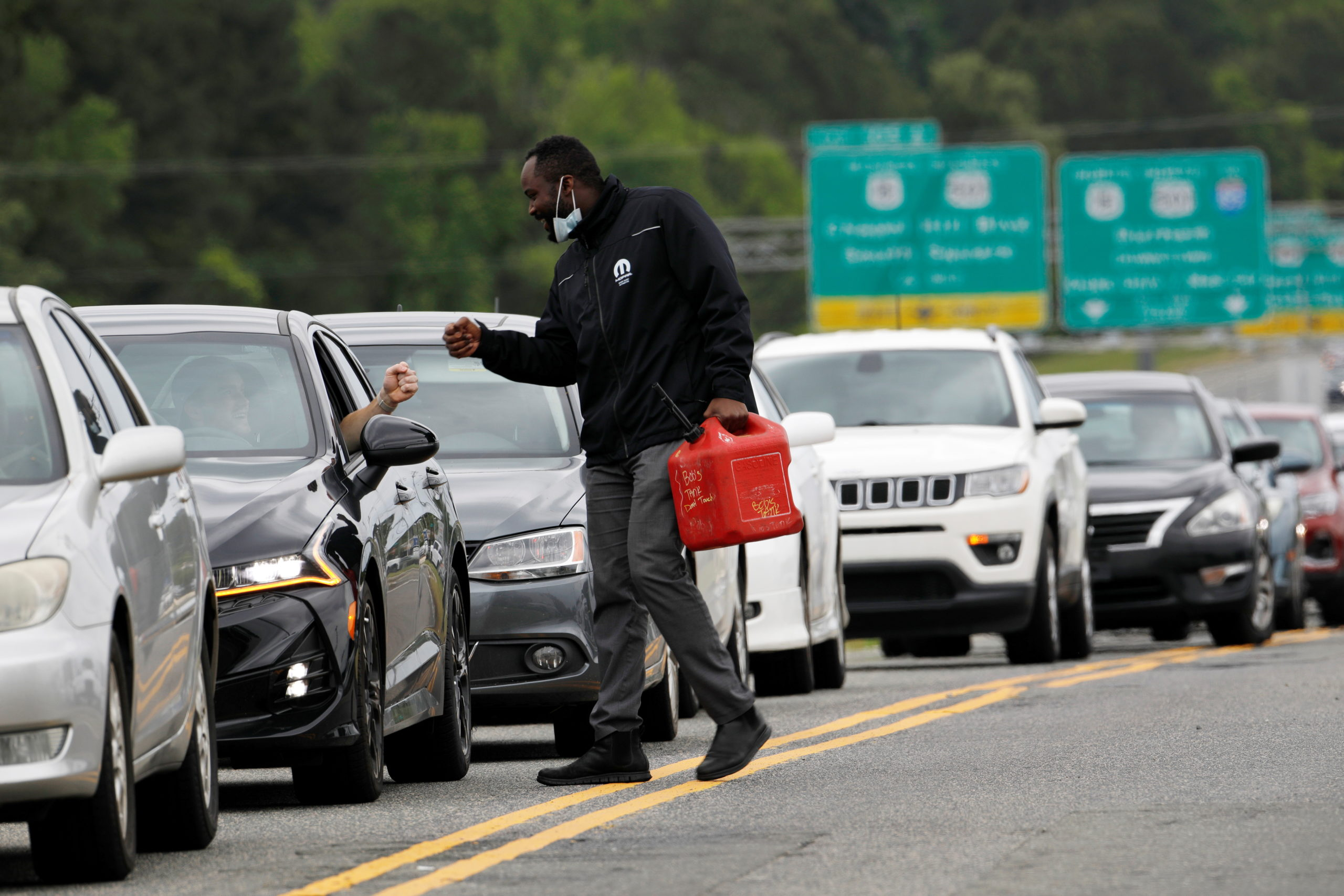 A friend carrying a gas container is greeted by a motorist waiting in a lengthy line to enter a gasoline station during a surge in the demand for fuel following the cyberattack that crippled the Colonial Pipeline, in Durham, North Carolina, U.S. May 12, 2021. (REUTERS/Jonathan Drake)