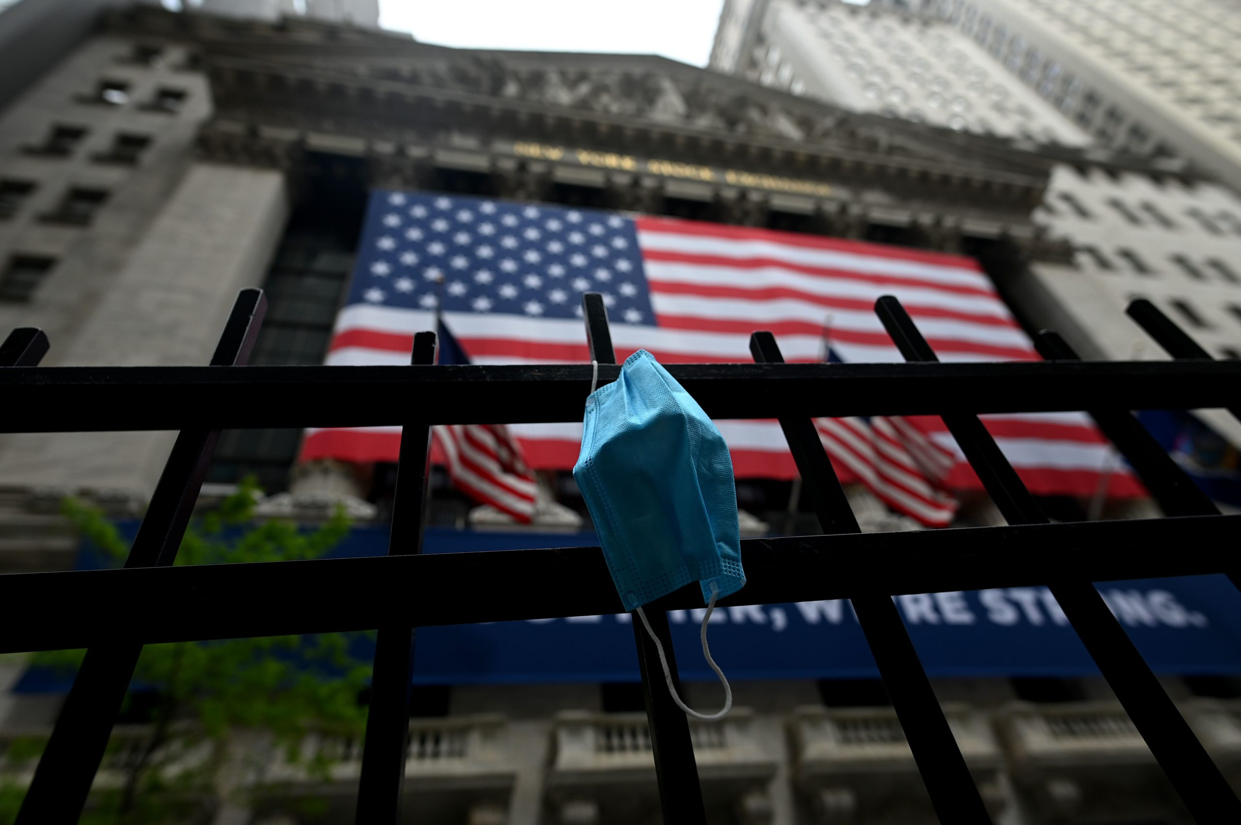 A face mask is seen in front of the New York Stock Exchange (NYSE) on May 26, 2020 at Wall Street in New York City. - Global stock markets climbed Monday, buoyed by the prospect of further easing of coronavirus lockdowns despite sharp increases in case rates in some countries such as Brazil. Over the weekend, US President Donald Trump imposed travel limits on Brazil, now the second worst affected country after the United States, reminding markets that while the coronavirus outlook is better, the crisis is far from over. (Photo by Johannes EISELE / AFP) (Photo by JOHANNES EISELE/AFP via Getty Images)