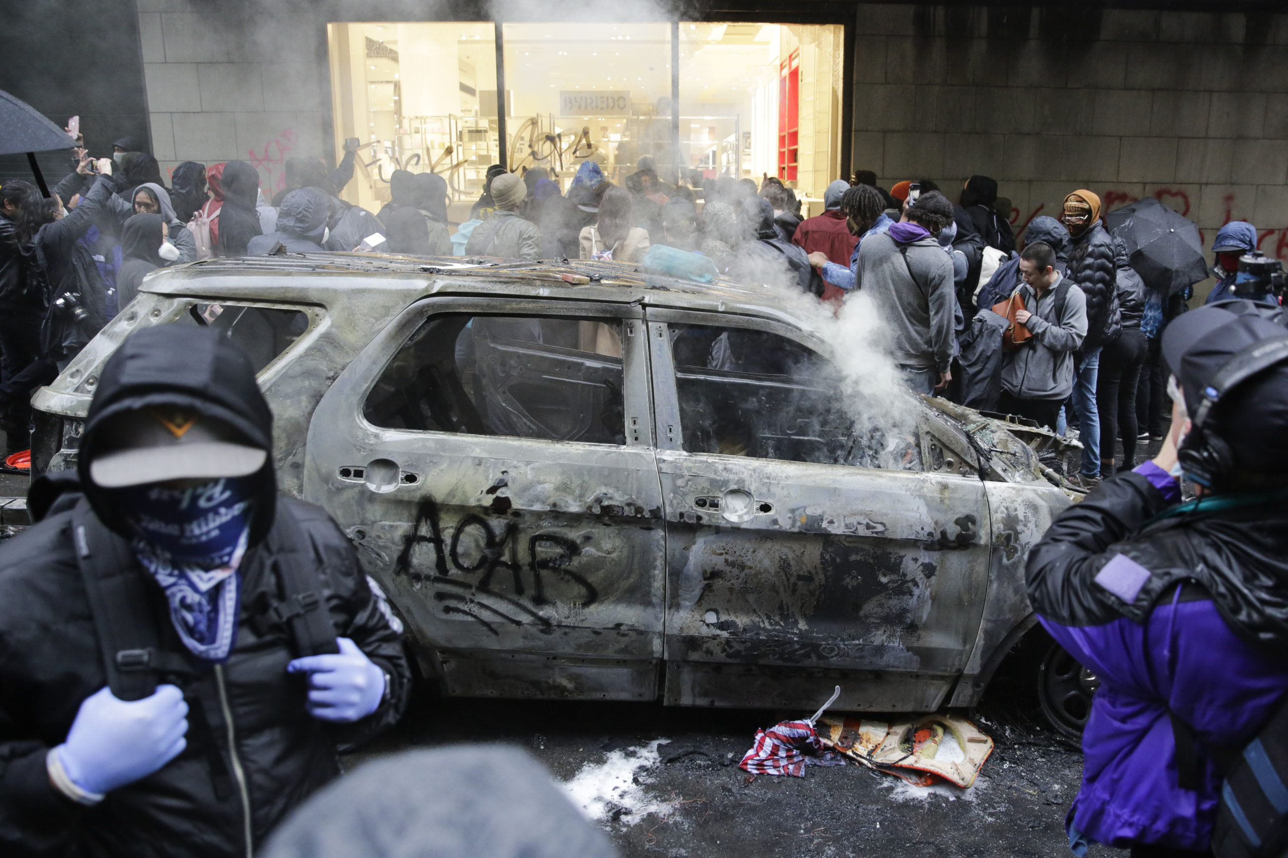 People loot a Nordstrom store near a burned police car in Seattle, Washington on May 30, 2020. (Jason Redmond/AFP via Getty Images)