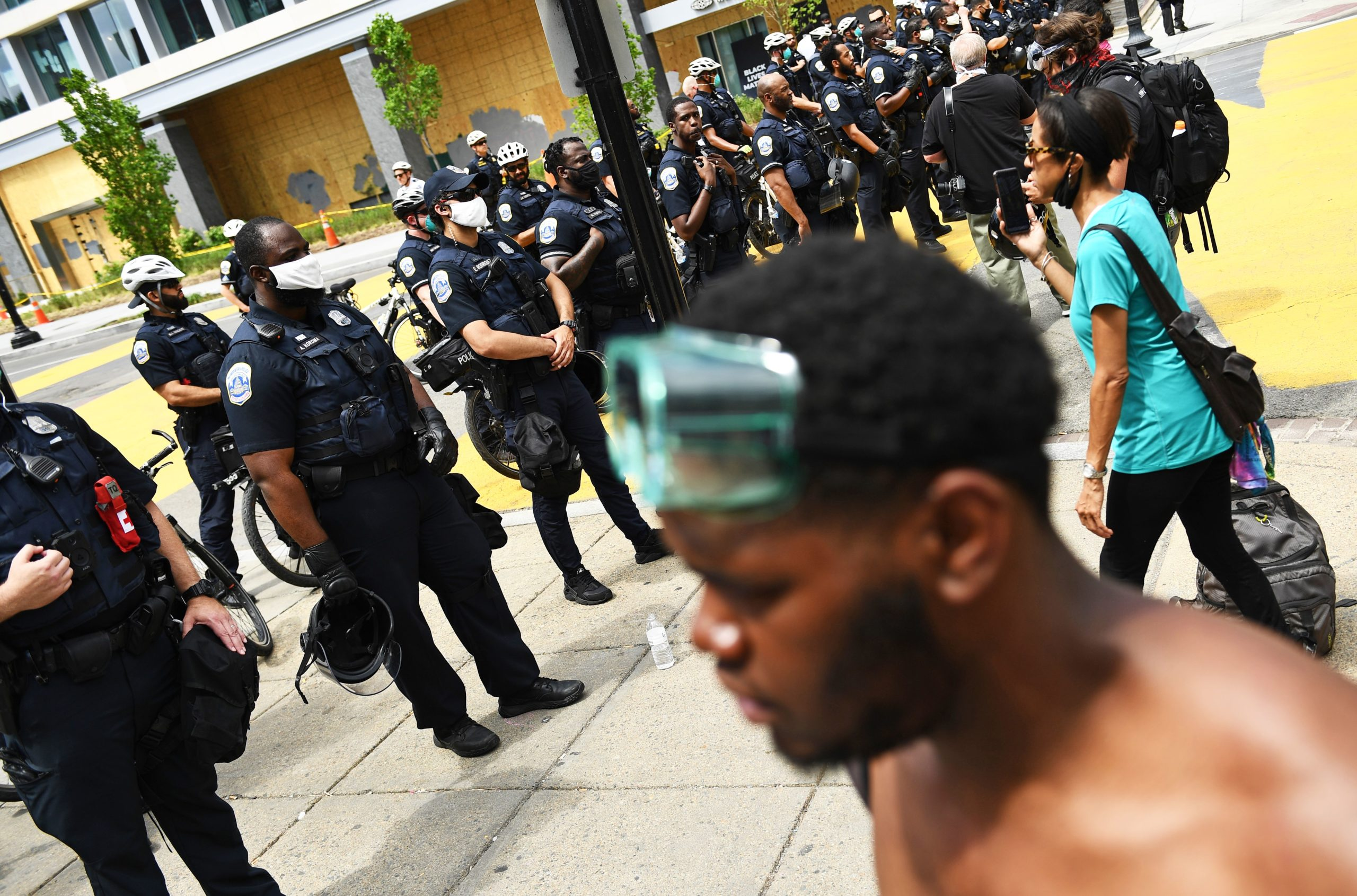 Protesters face a line of police officers in riot gear as they form a security perimeter in Washington, D.C. on June 23. (Brendan Smialowski/AFP via Getty Images)